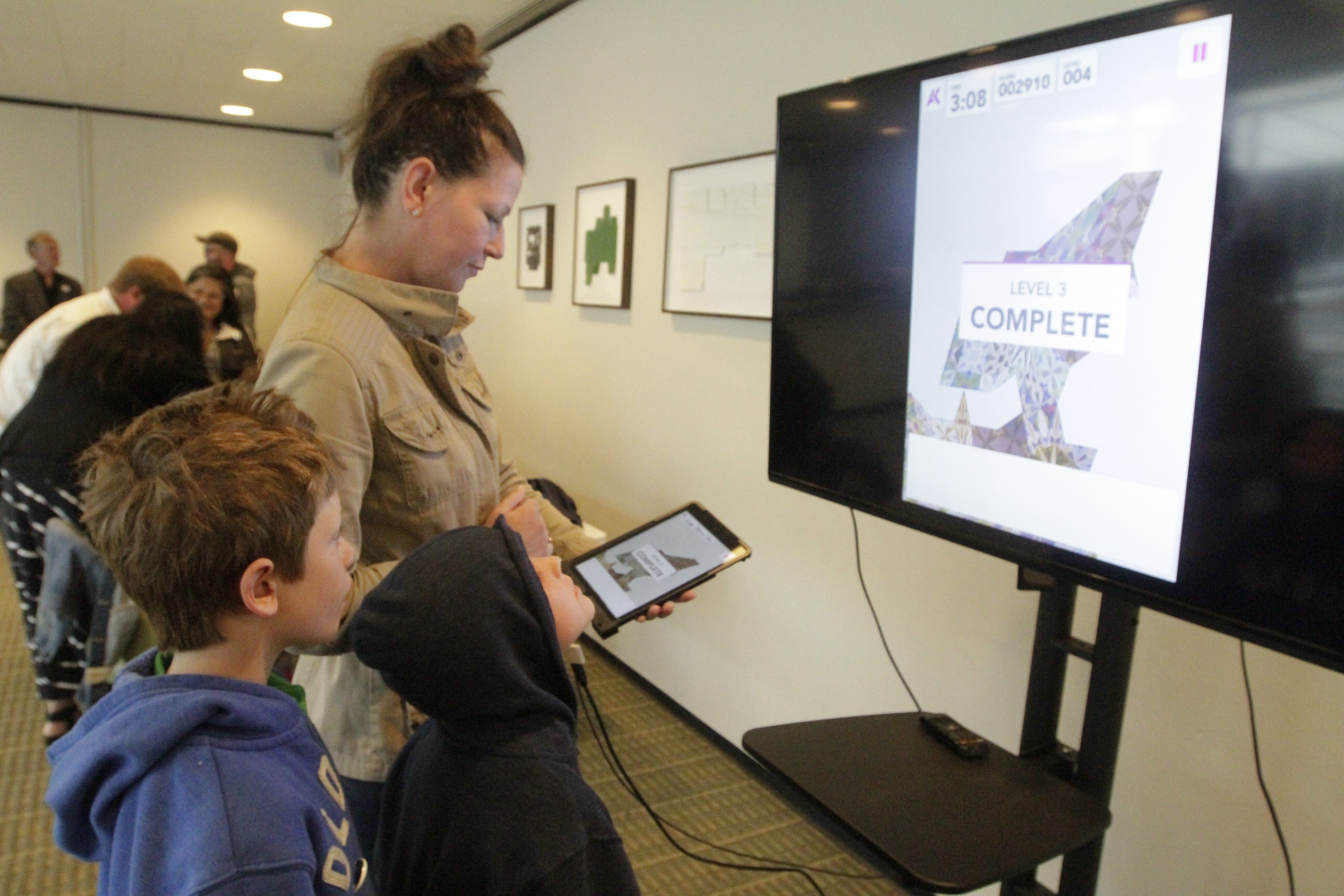 Jennifer Tober, of Hamburg, and her two children Caden, 8, left, and Lawson, 6, play with ArtGames 2.0, a newly developed gaming app at The Albright-Knox Art Gallery. The recently released game seeks to engage 'tweens in eight artworks on display at the gallery.