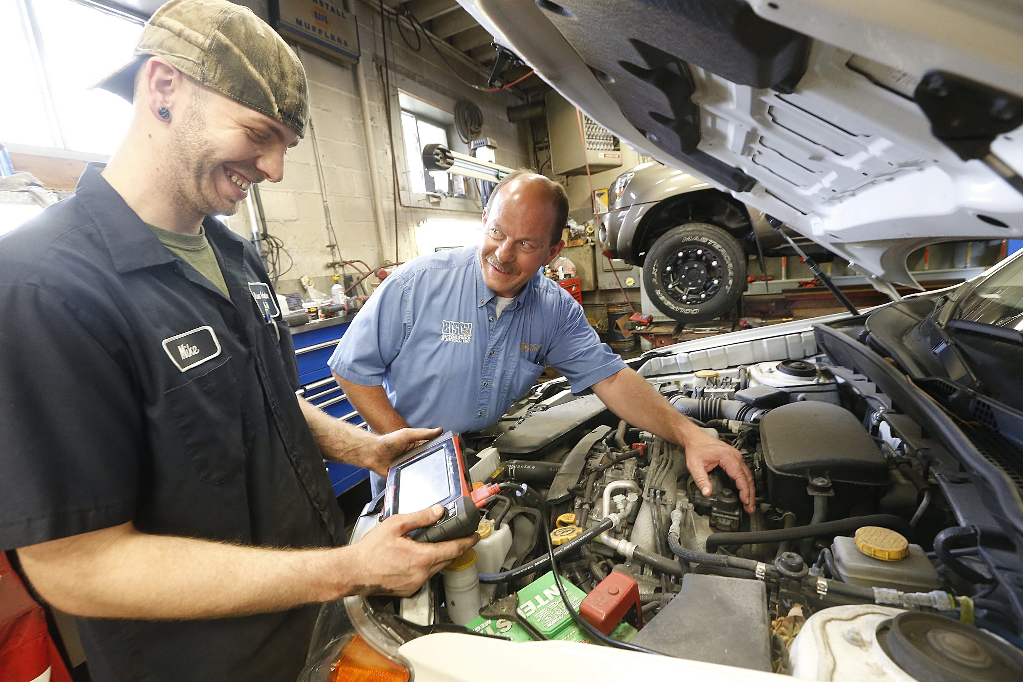 Owner Bob Gugino, right, and mechanic Mike Heinbaugh diagnose an engine problem on a customer's car with a computerized scanner at Bison Automotive on Kenmore Avenue in Kenmore. New car repairs require mechanics who can use wrenches - and computers.
