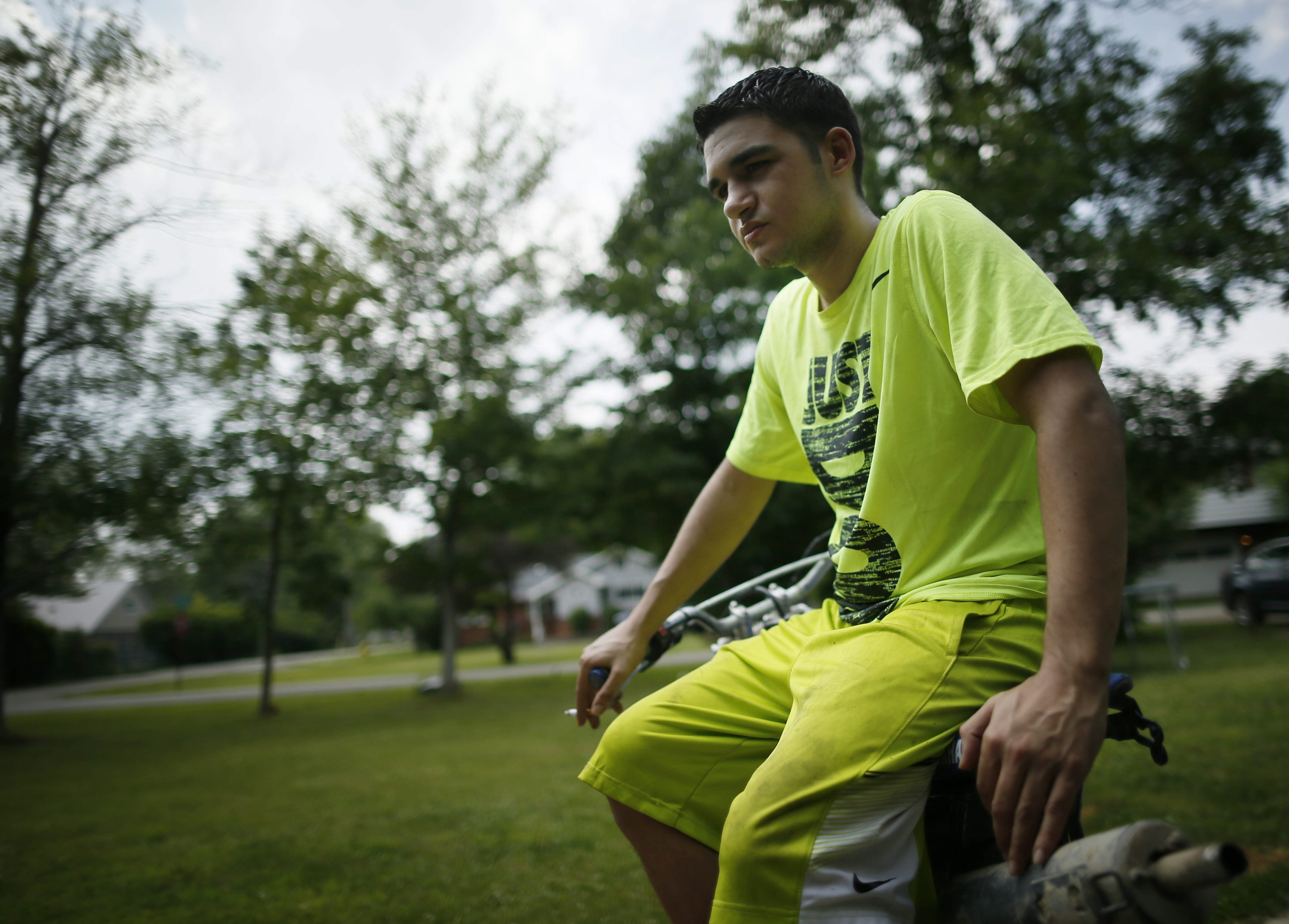 Nicholas Harris, whose biological father, Richard Matt, was shot and killed by federal agents while he was on the run after escaping from prison, pauses to reflect while working on his dirt bike outside his Angola home Tuesday.