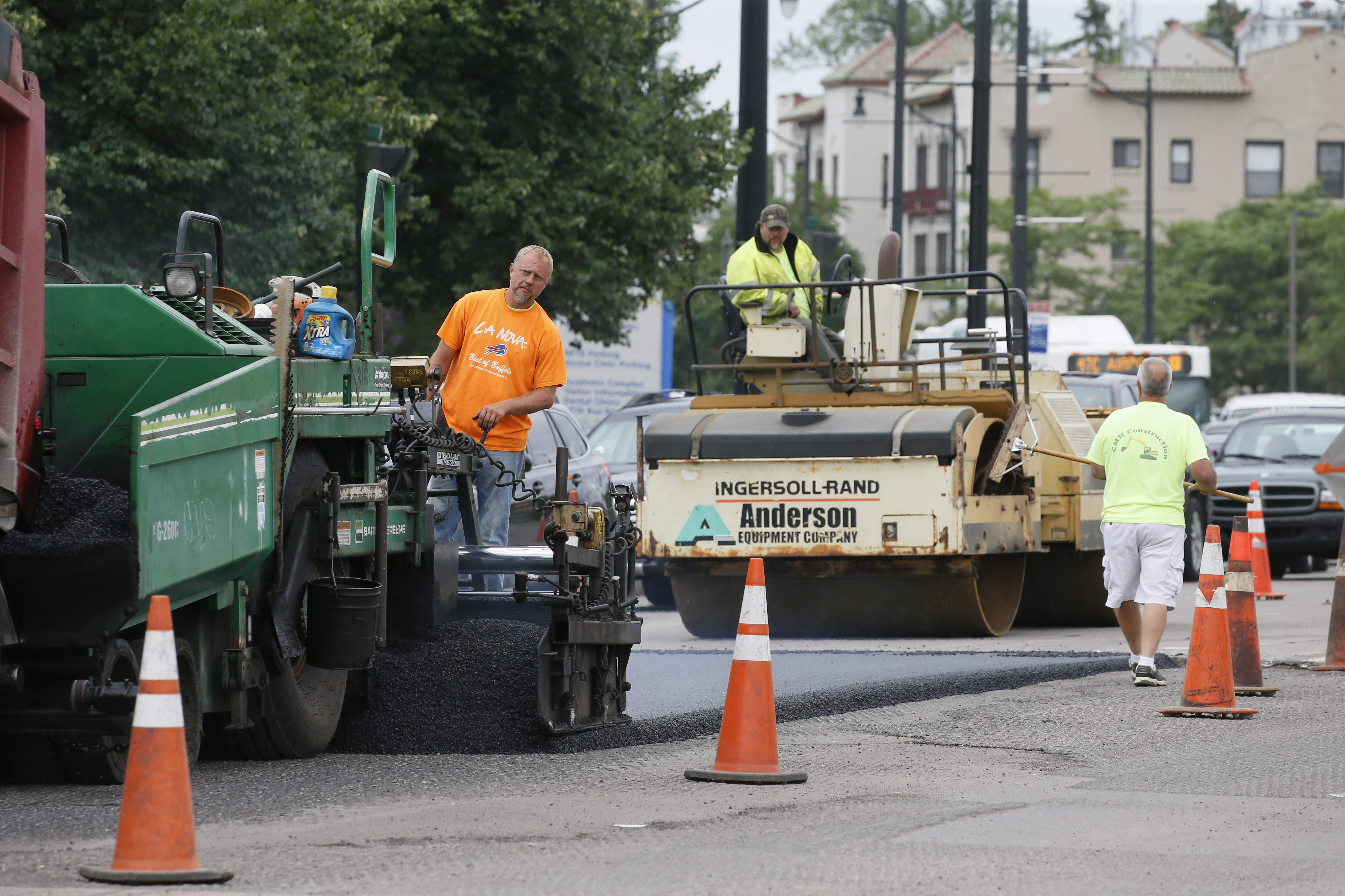 A city work crew paves the outbound lanes of Main Street between Bailey and Kenmore avenues on Thursday morning.