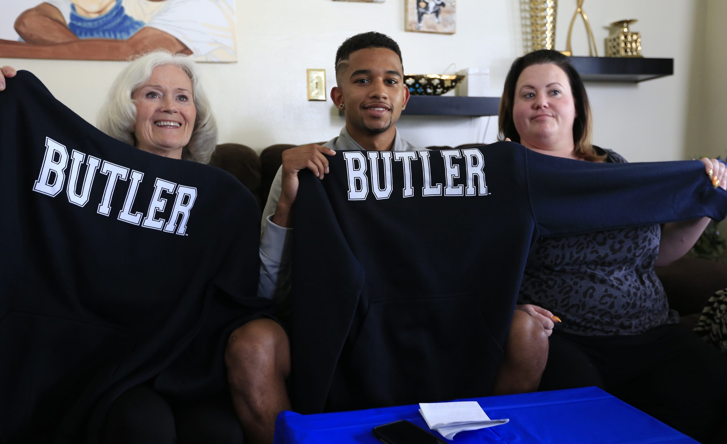 Howard Washington, center, announces his decision with his grandmother Joan Crawford, left, and mother Kacey by his side. Watch video at buffalonews.com.
