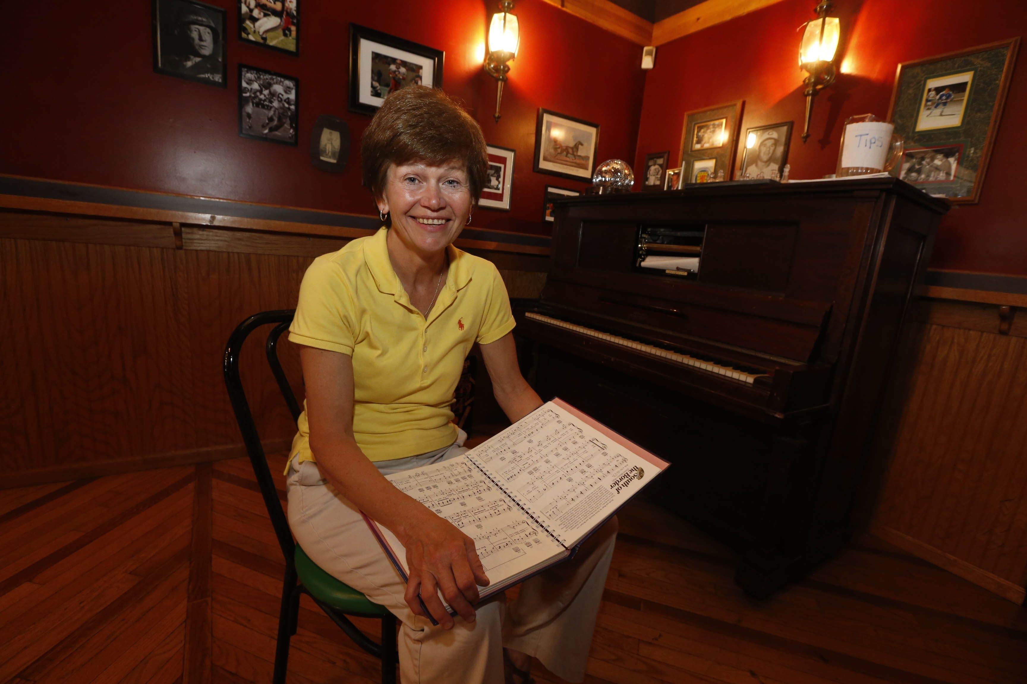 Claudia Andres looks over some sheet music in the Mug and Musket, the Youngstown restaurant she and her partner opened on Labor Day weekend.