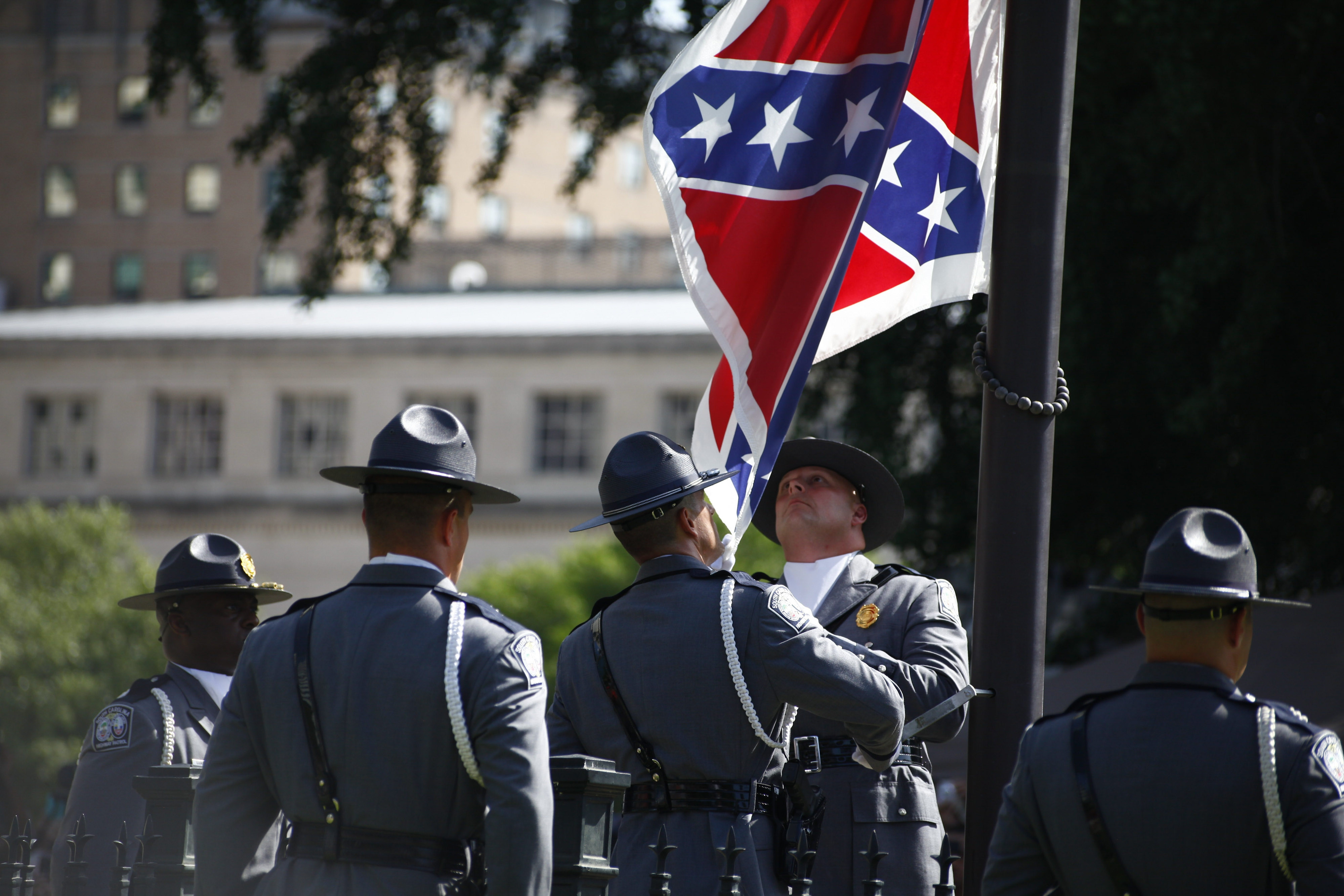 Members of the South Carolina State Police remove the Confederate battle flag from the grounds of the Statehouse in Columbia, S.C., Friday. (New York Times photo)