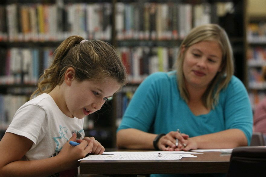 Orchard Park teacher Karen Connolly does reading and writing exercises with Rory Etheridge, 9, at the Orchard Park Public Library last week. The topic of keeping a child's  brain fresh during summer vacation will be discussed at 12:30 p.m. today during Refresh Mondays. (Sharon Cantillon/Buffalo News)