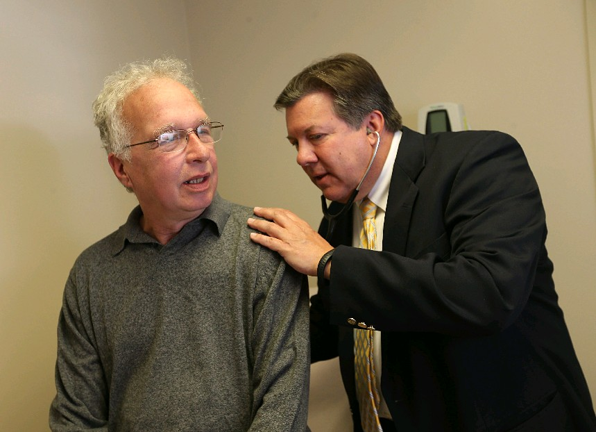 Dr. Richard Vienne, right. examines patient Patrick Kerr last month at the Amherst Health Care Center. (Sharon Cantillon/Buffalo News)