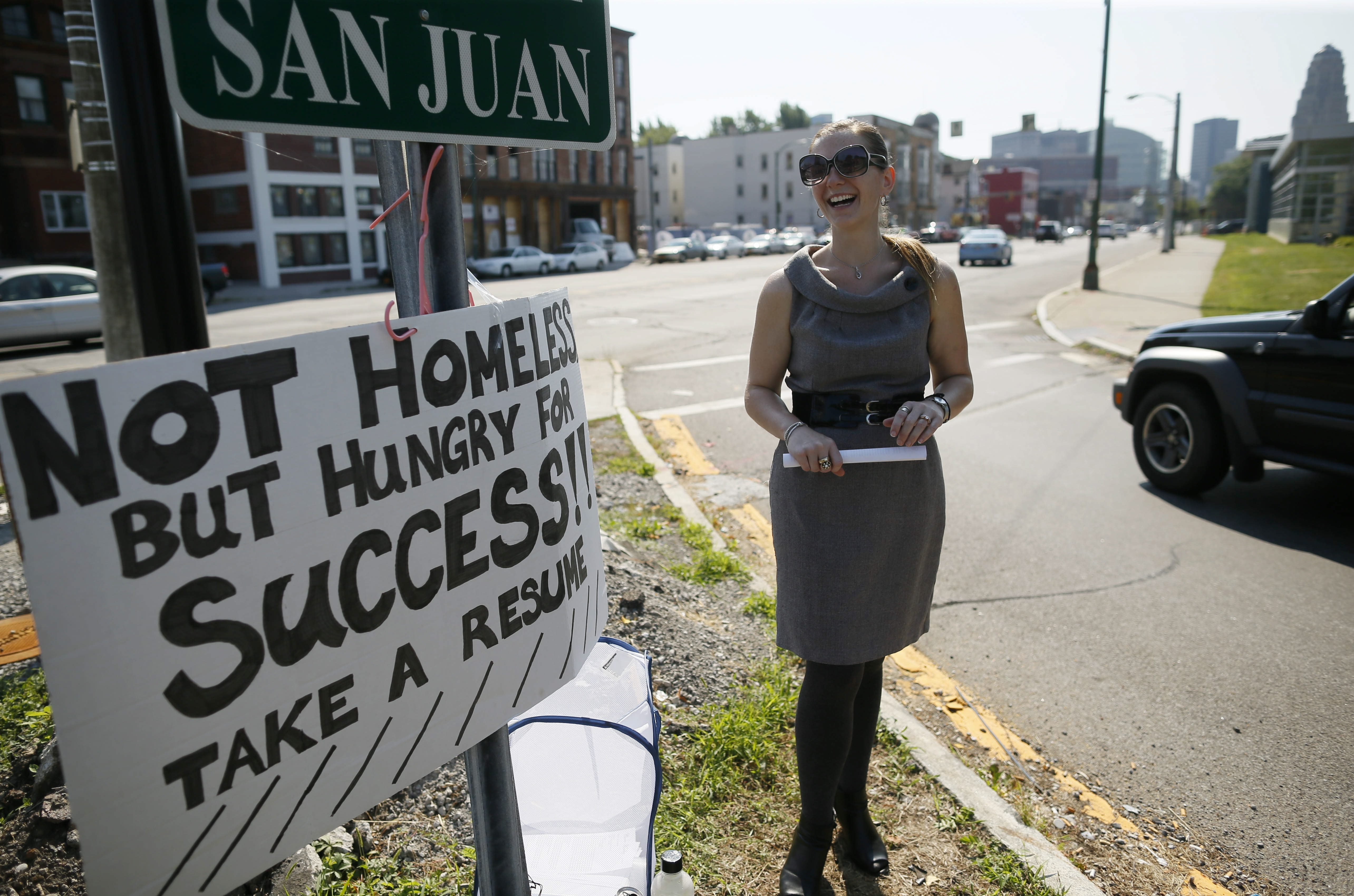 Carrie Kemeling takes her unconventional job search to the Niagara Street off-ramp from the I-190 on Monday.
