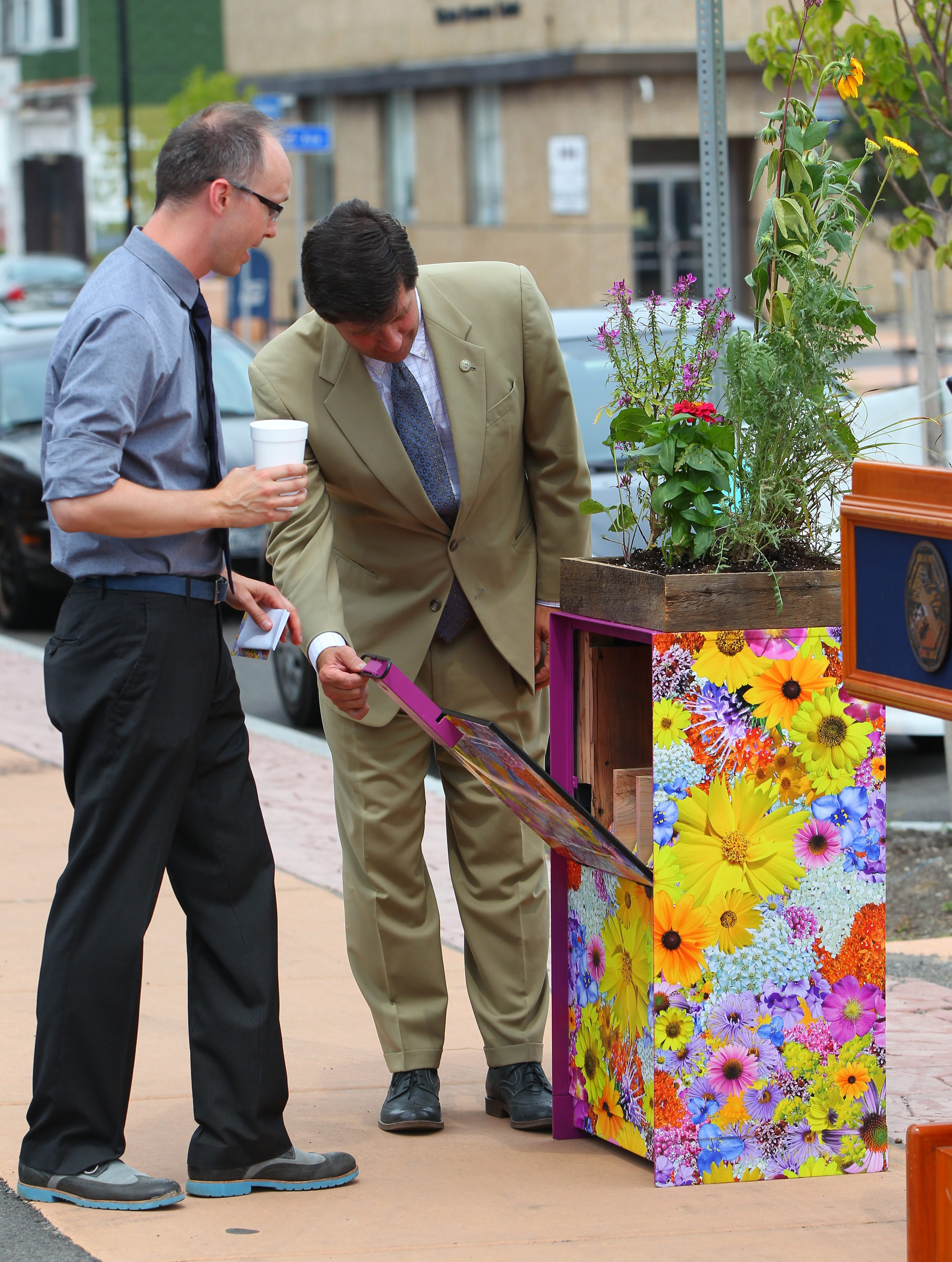 Erie County Executive Mark C. Poloncarz, right, and Albright-Knox Curator of Public Art Aaron Ott look at a special newspaper box filled with wildflower seeds before a news conference on Fillmore Avenue in Buffalo on Monday.