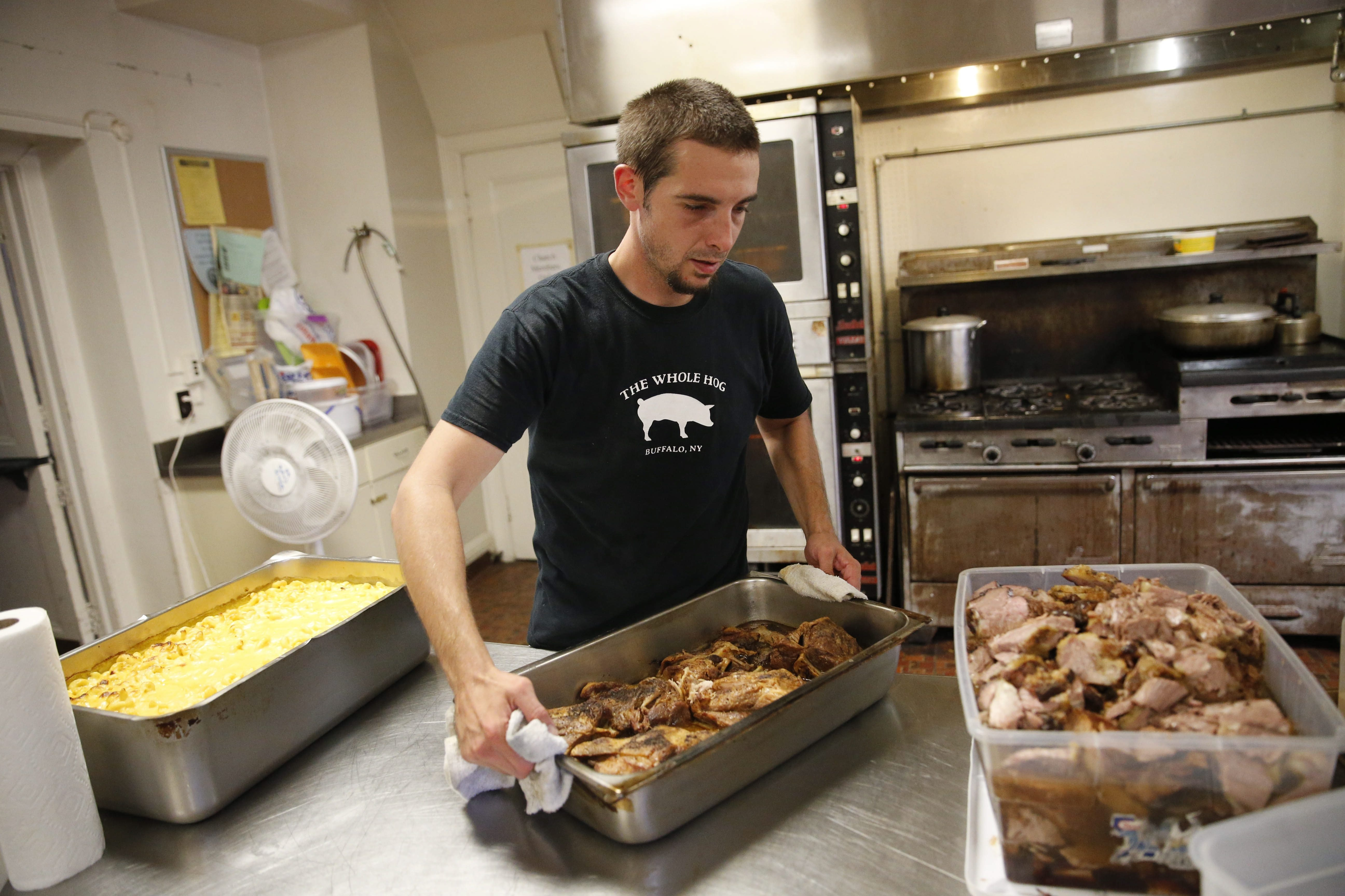 Matthew Simpson, a cook for the Whole Hog food truck, prepares food for the day's run in the kitchen at St. John's Grace Episcopal Church on Tuesday.