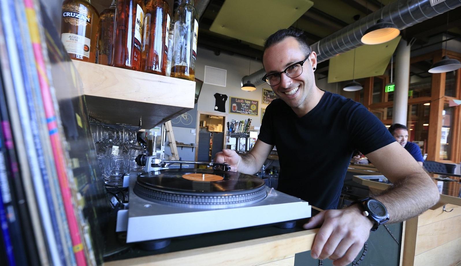 Handlebar Pub bartender Adam Rath plays vinyl records on Swan Street in downtown Buffalo. (Harry Scull Jr./Buffalo News)
