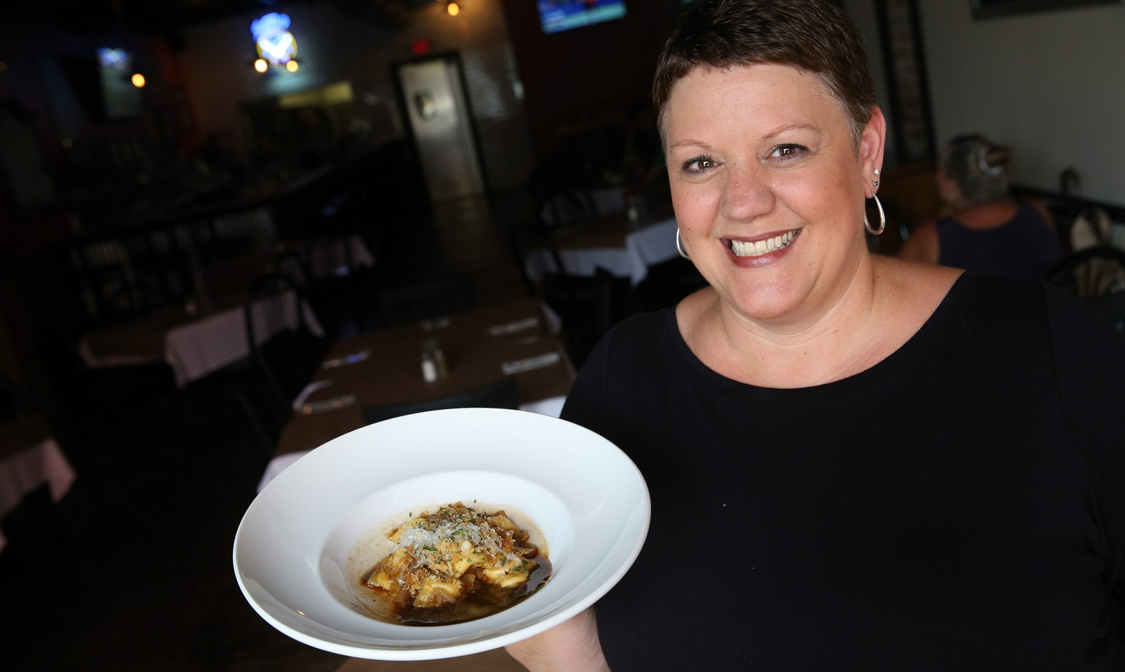 The Mess Hall server Sue Staniszewski – now the owner – presents the homemade french onion raviolettis. (Sharon Cantillon/Buffalo News)