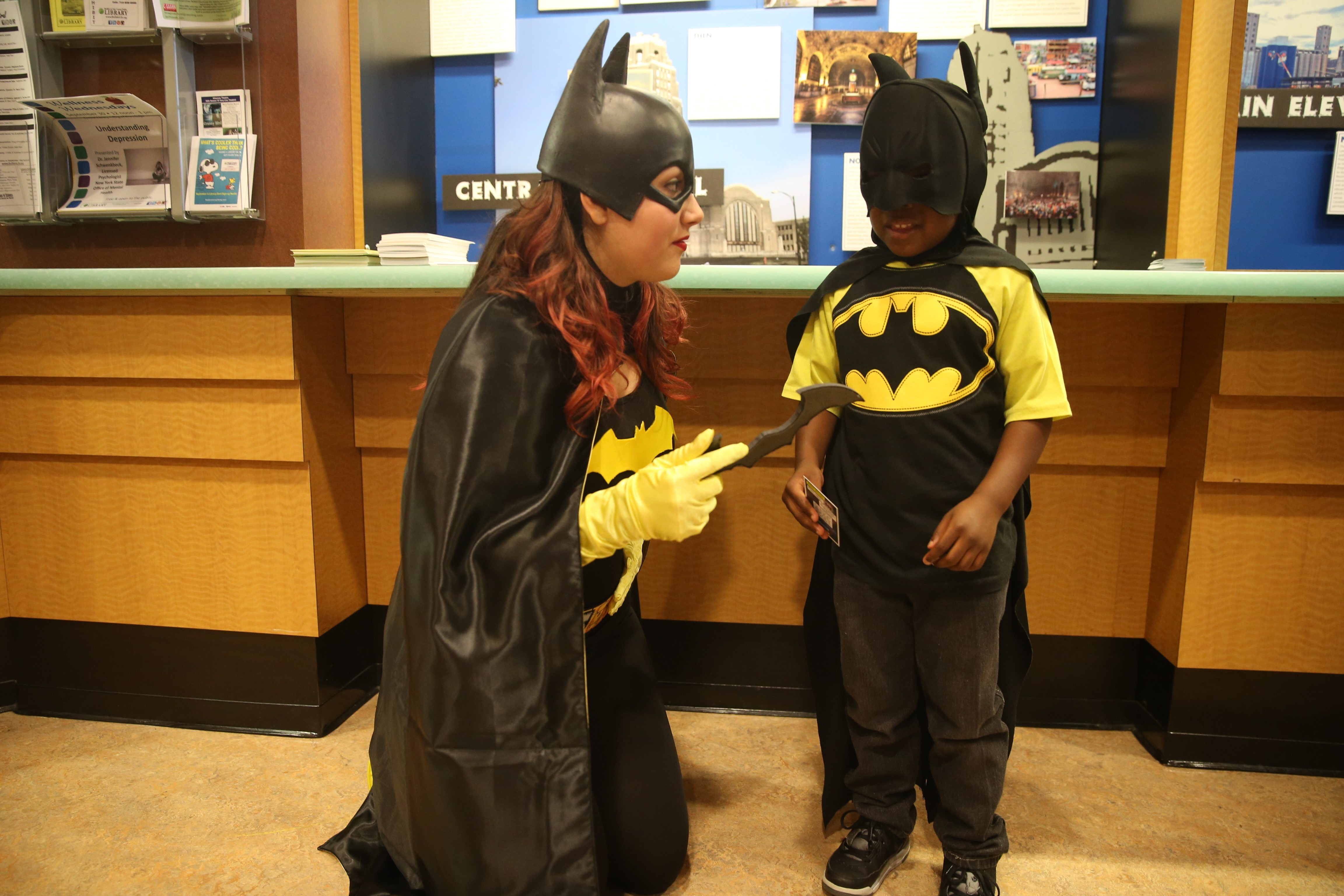 Batgirl (Lyana Macaluso) talks with a young Batman (Quince Foster, 4) at Batman Day, an event aimed at fighting bullying, held Saturday at the Buffalo & Erie County Central Library, in Buffalo.     John Hickey/Buffalo News