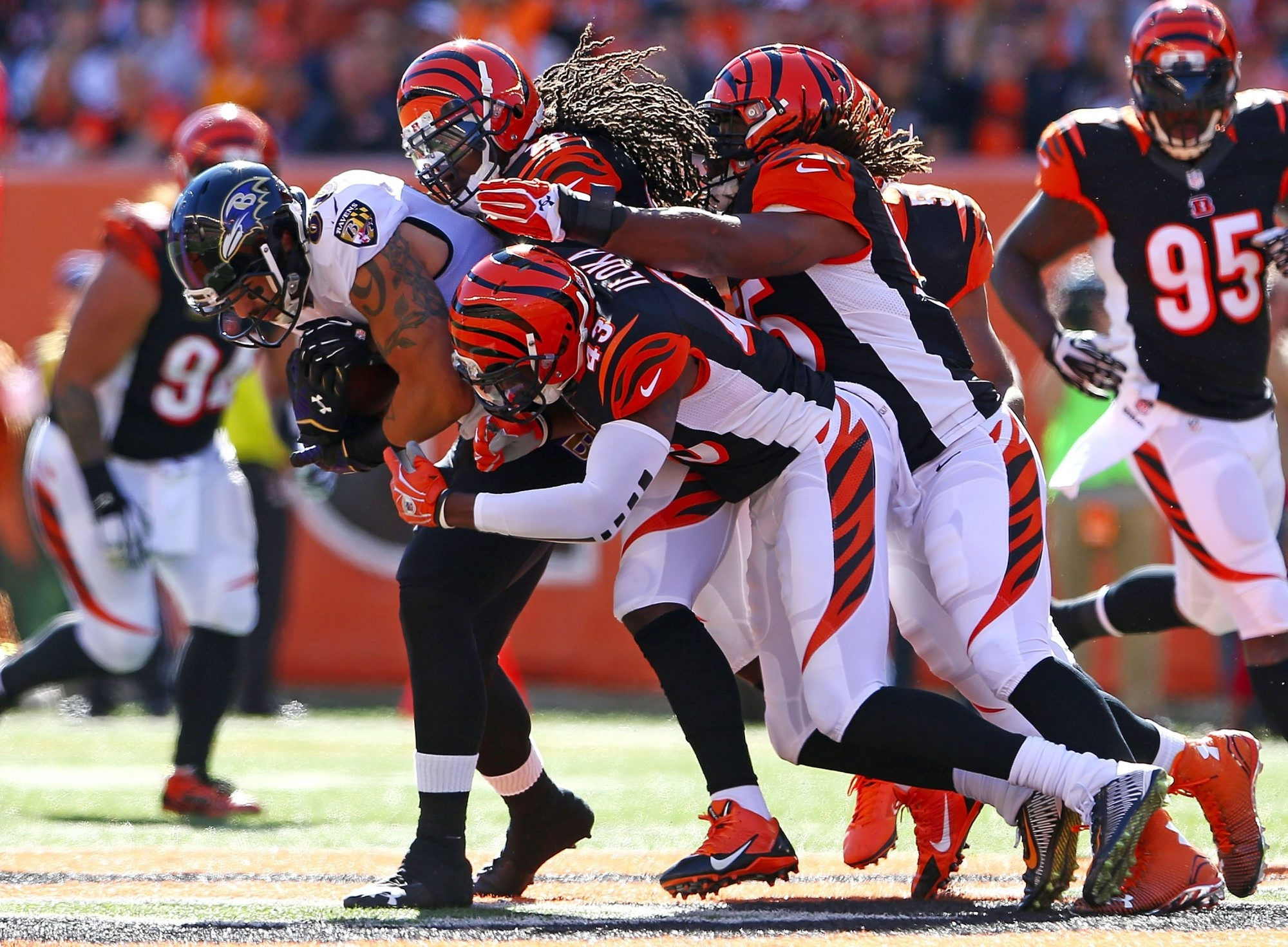 Crockett Gillmore of the Ravens is gang tackled by Bengals defenders in their meeting last October. Cincinnati swept the season series in 2014.