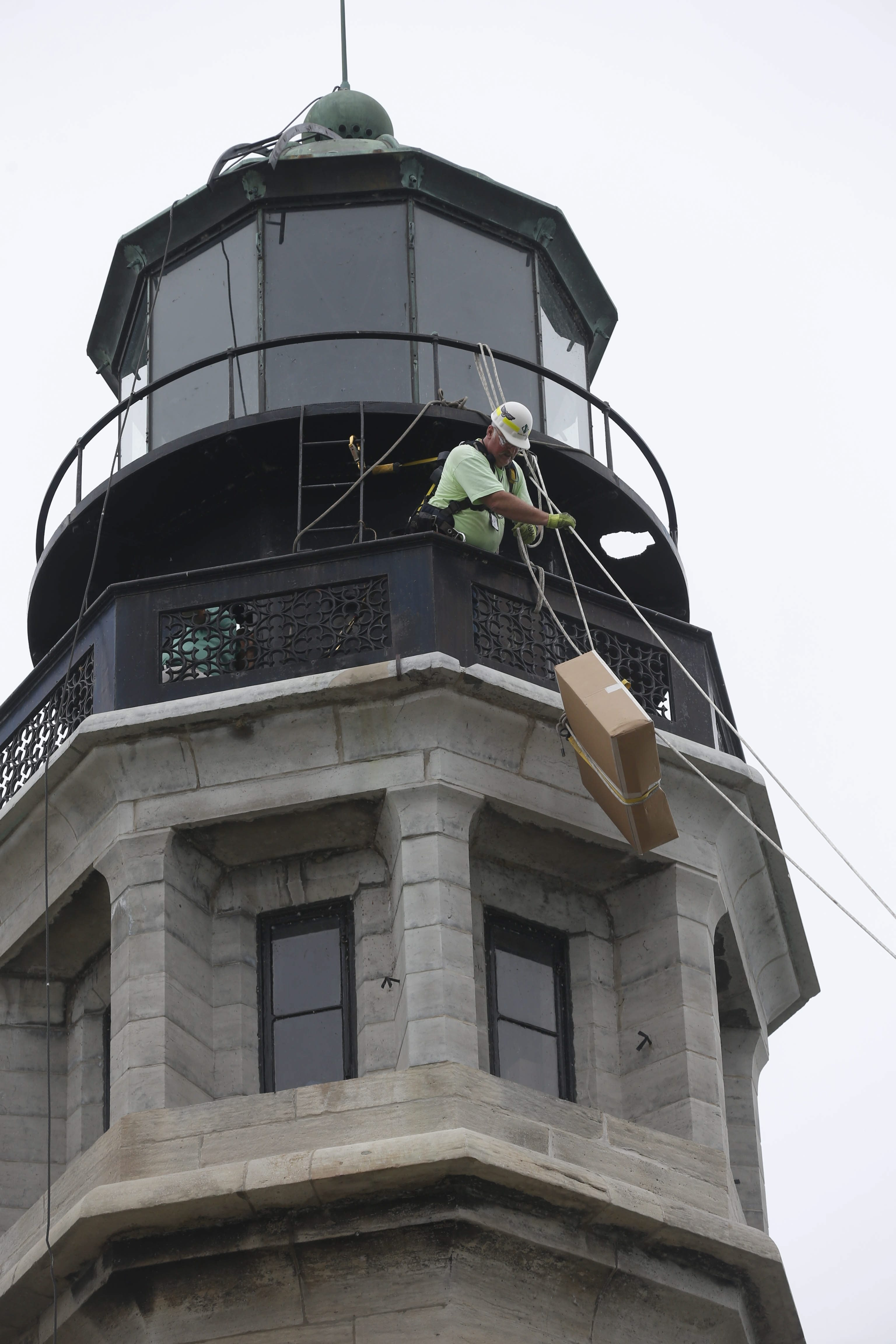 Rob Vizza, with International Chimney Corp., uses a block-and-tackle system to hoist components up to the Buffalo Light on Buffalo on Monday.