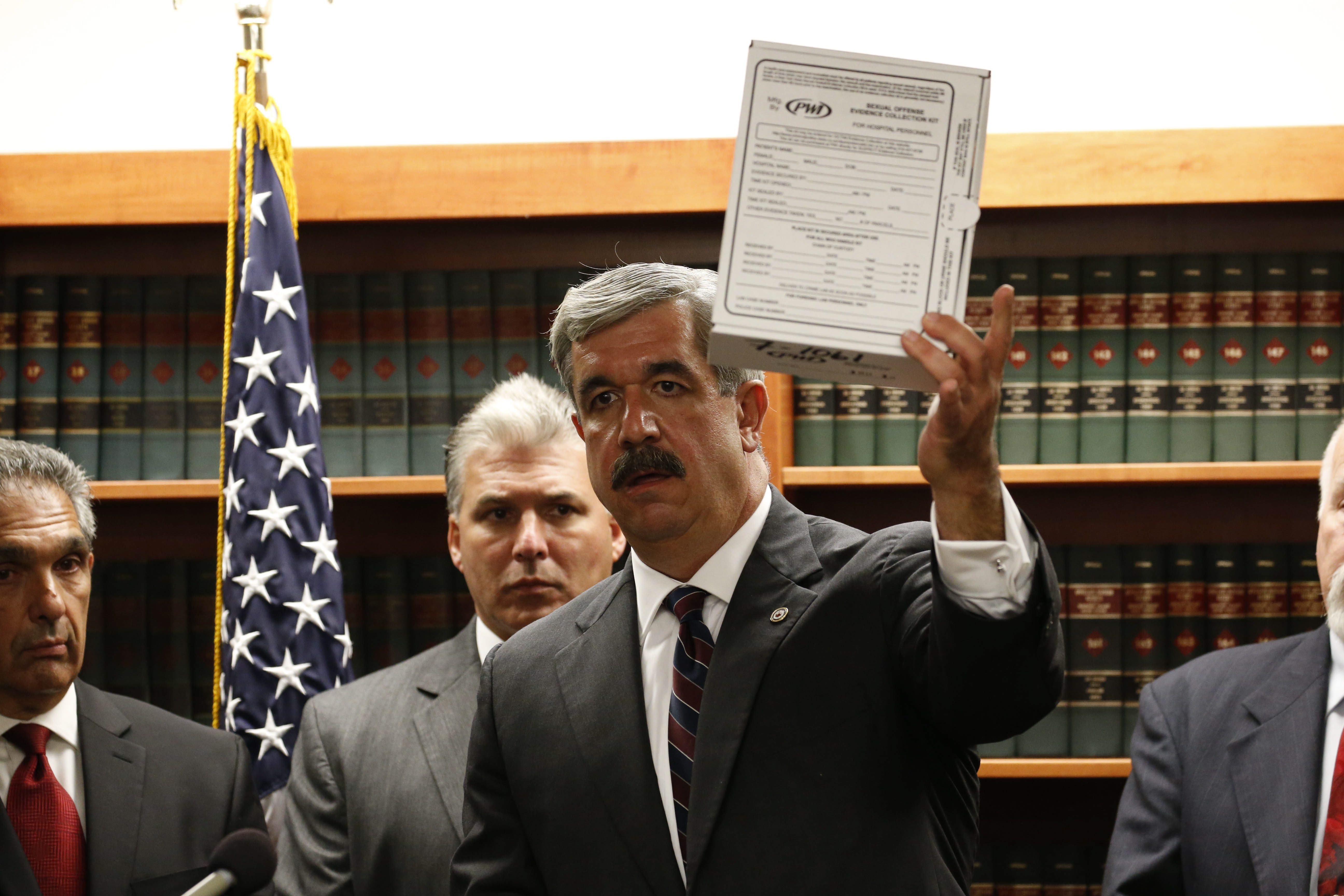 "Erie County District Attorney Frank Sedita III holds up a ""rape kit"" evidence box as he addresses reporters during a press conference Friday in his office."