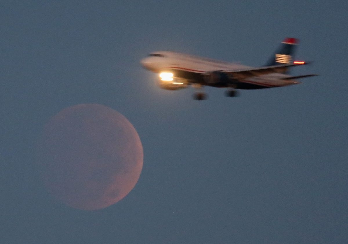 An airliner on approach to Reagan National Airport flies past the full moon during a lunar eclipse last fall as seen from Washington, D.C. If  thick cloud cover holds off over Western New York, the view Sunday night may be just as spectacular.