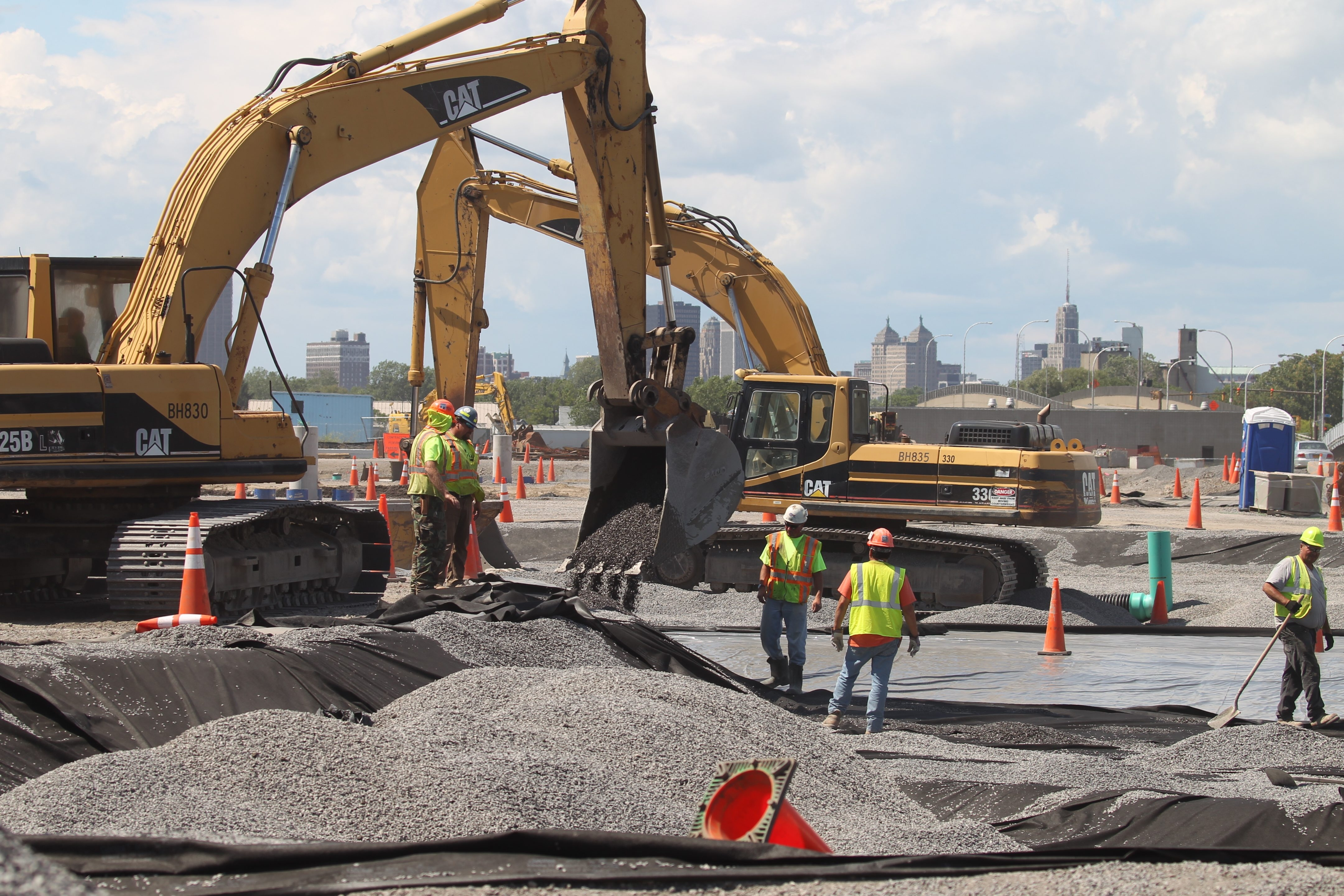 Contruction crews work on a water retention pond for a parking area as work goes on at SolarCity on Aug. 4, 2015. (John Hickey/News file photo)