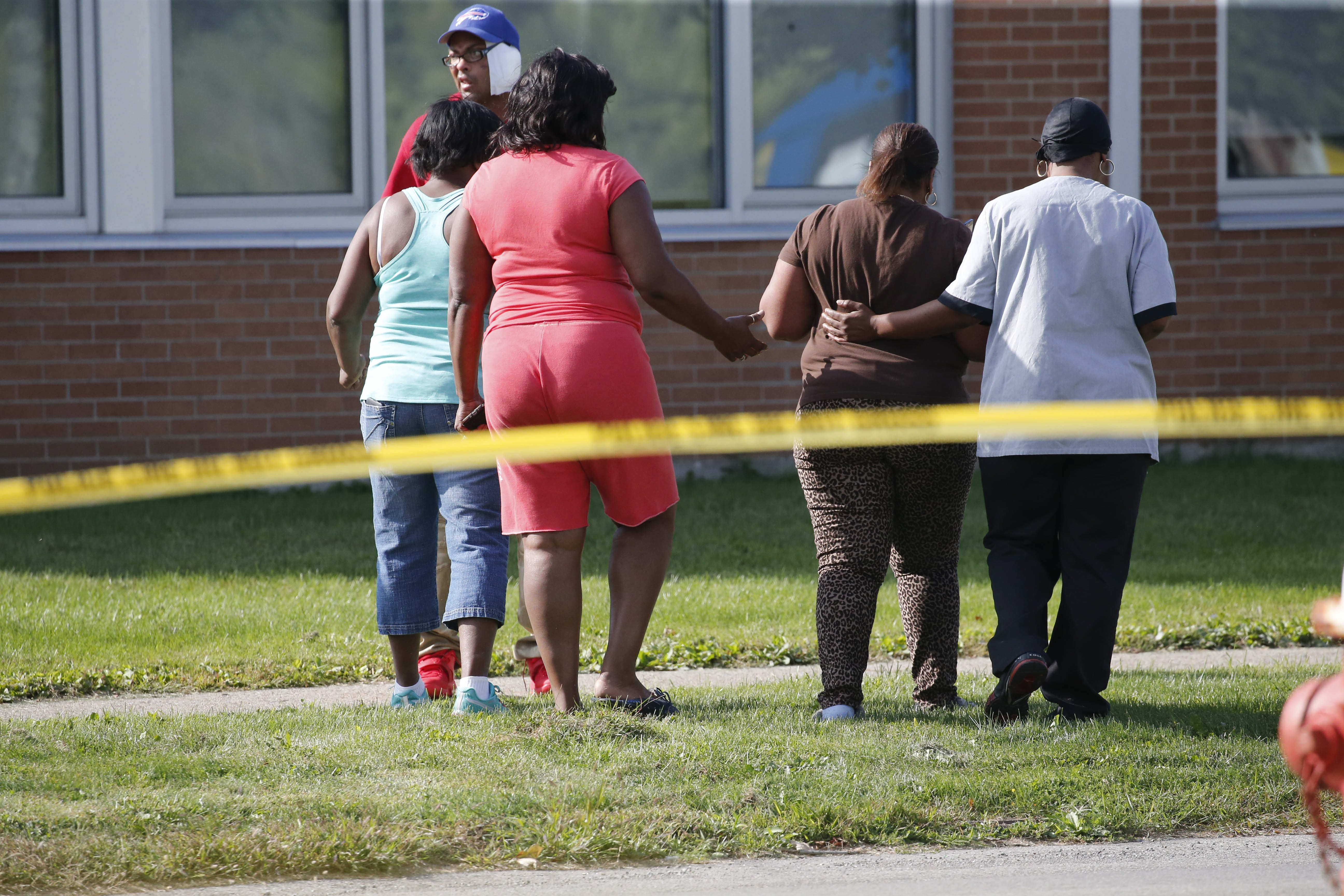 Family members grieve as Buffalo Police investigate at the scene of a homicide on Woodlawn Avenue outside Buffalo Academy of Visual and Performing Arts, Thursday, Sept. 24, 2015.  The victim was shot inside a vehicle at the intersection of Masten and Woodlawn.  (Photo by Derek Gee / Buffalo News)