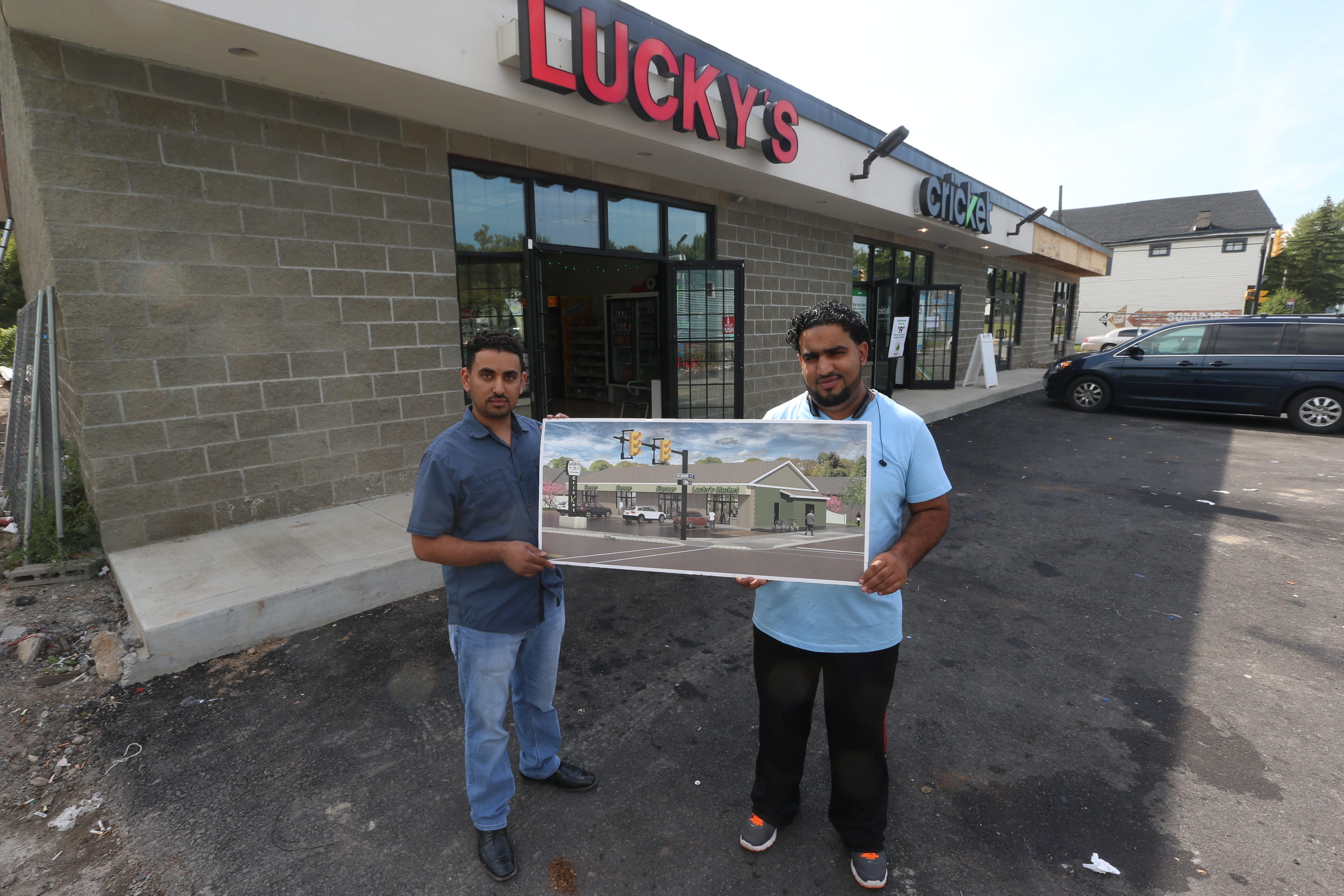 Ali Majid, left, and his cousin Fadel Alhajjaji hold an image of their newly expanded shopping plaza on Sycamore Street.