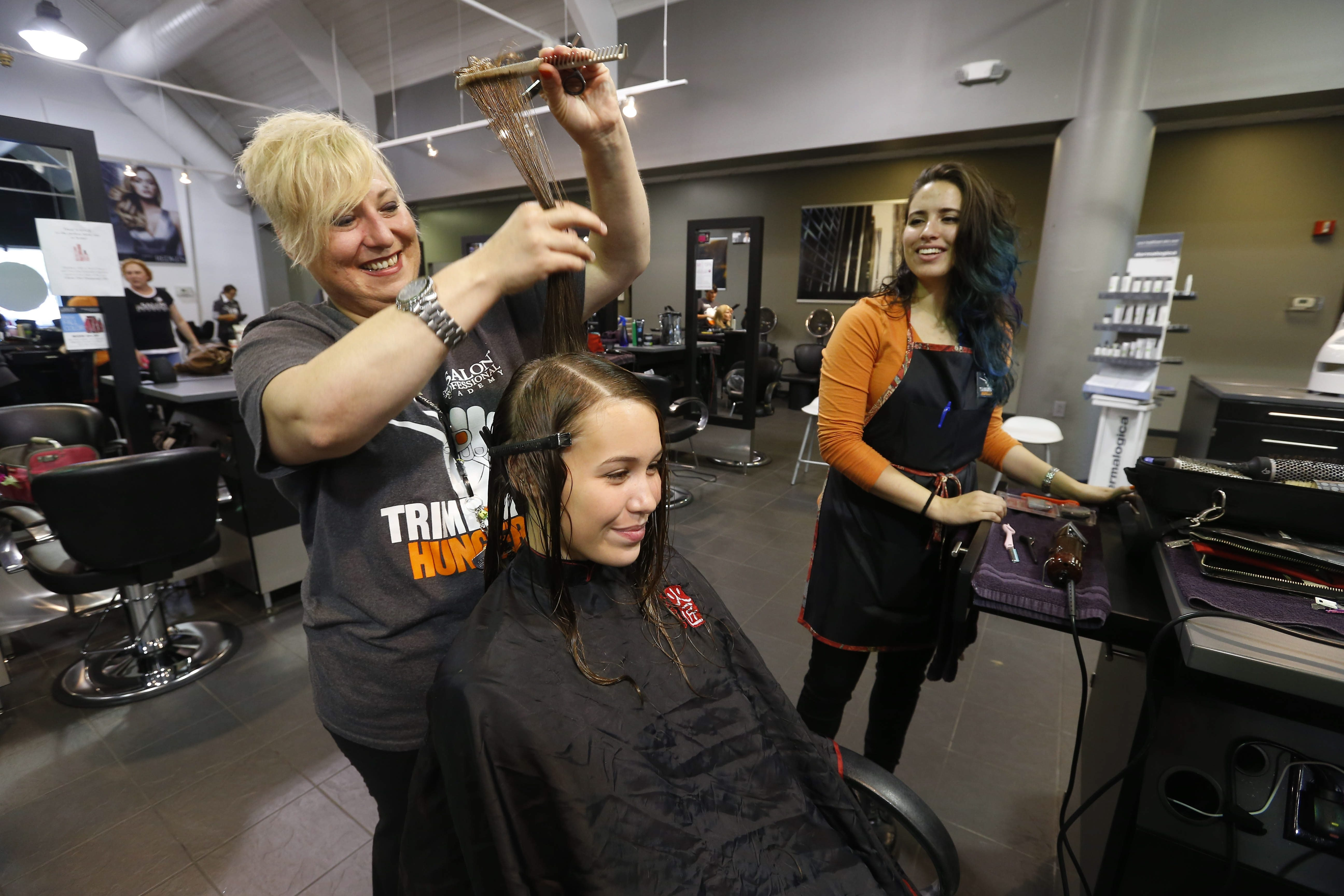 Natalie Morrow, center, has her hair cut by stylist Kate Meginley, left, and student Angelina Sanchez, right, for the Trim Hunger nationwide fundraiser at Salon Professional Academy in the Town of Tonawanda on Sunday.
