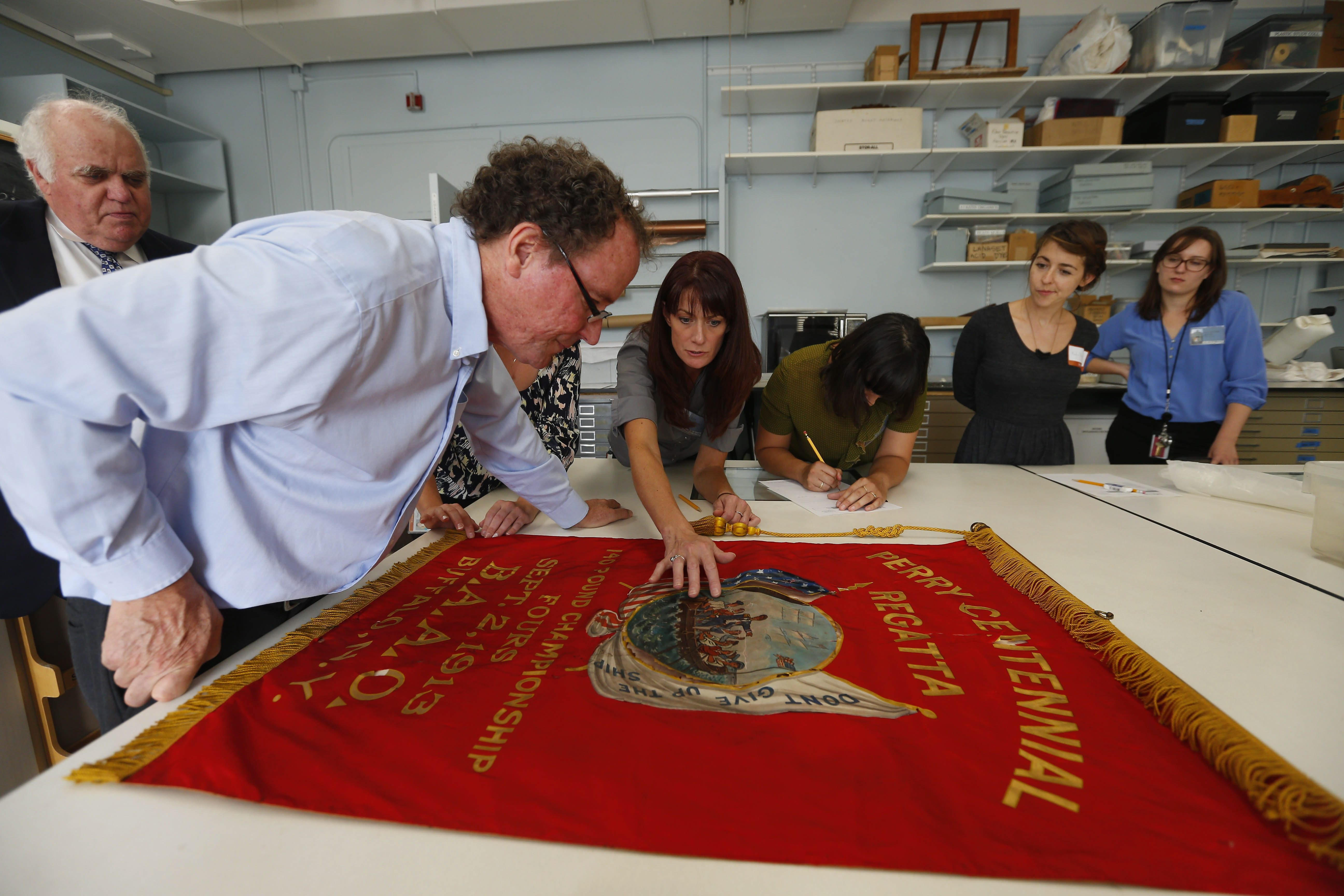From left, Gabriel Ferber, of West Side Rowing Club, looks on as SUNY Buffalo State Professor Jonathan Thornton and his art restoration graduate students look over the club's old banners.