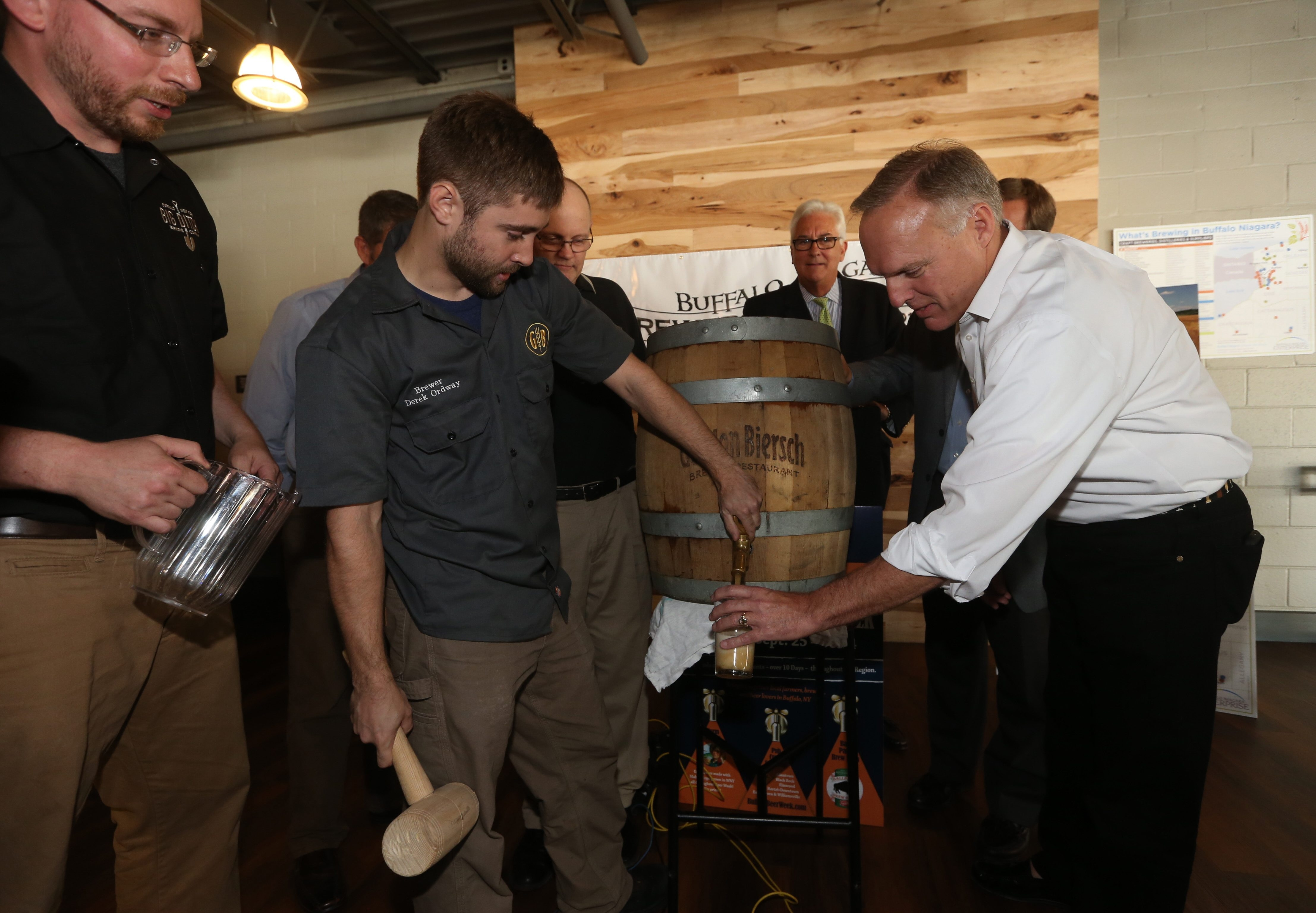 Matt Kahn, left, of Big Ditch Brewing, watches Derek Ordway, head brewer of Gordon Biersch, tap a keg with Neil Kavanaugh of Consumer Beverages at a keg-tapping ceremony at Big Ditch Brewery to kick off the sixth annual Buffalo Beer Week on Tuesday.