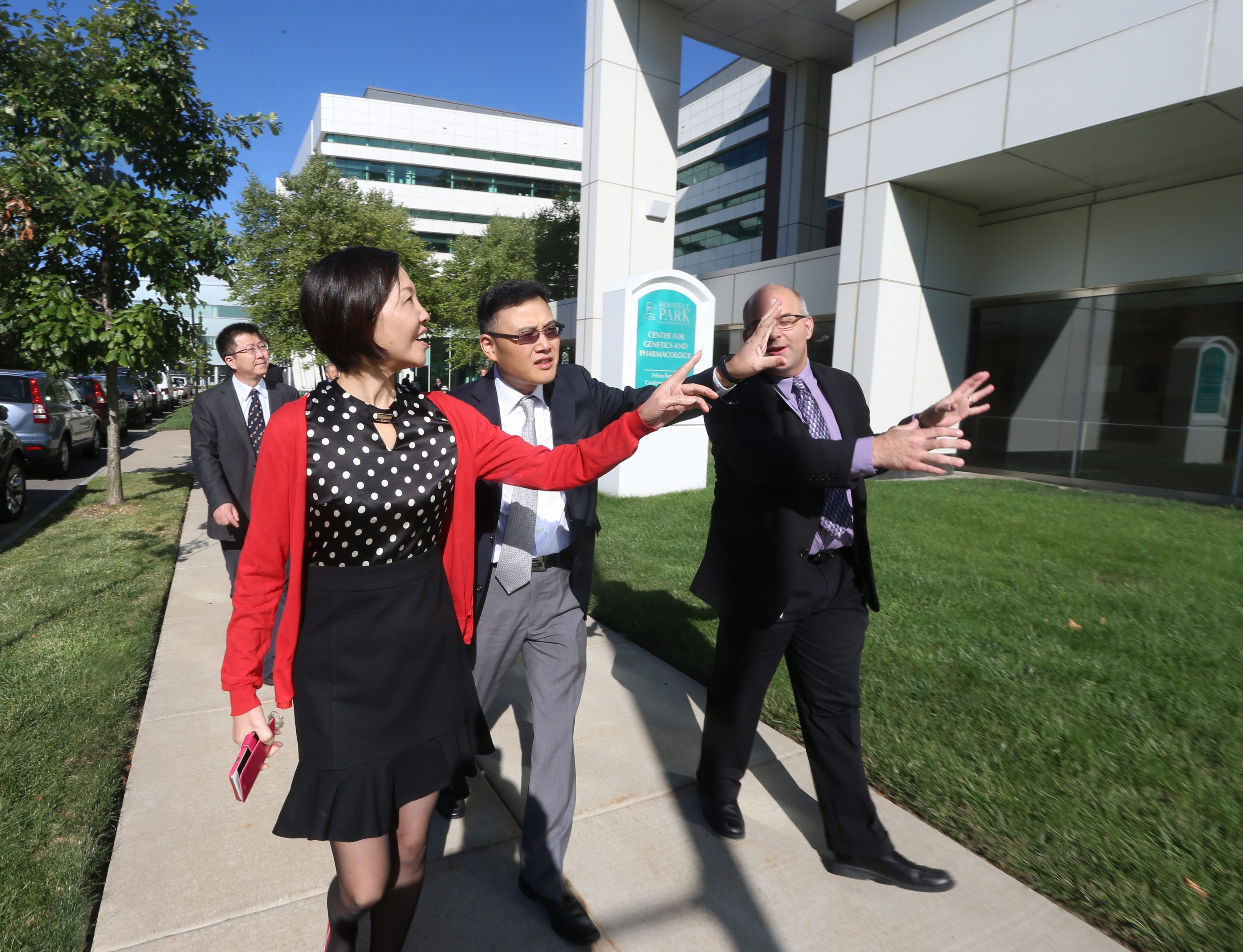 Yang Liqiong, foreground, deputy director general of Chongqing's Economic Development and Information Commission, tours Roswell Park's Center for Genetics and Pharmacology with officials including William Zuo, center, of Polymed, and Gerald Fetterly, of Athenex.