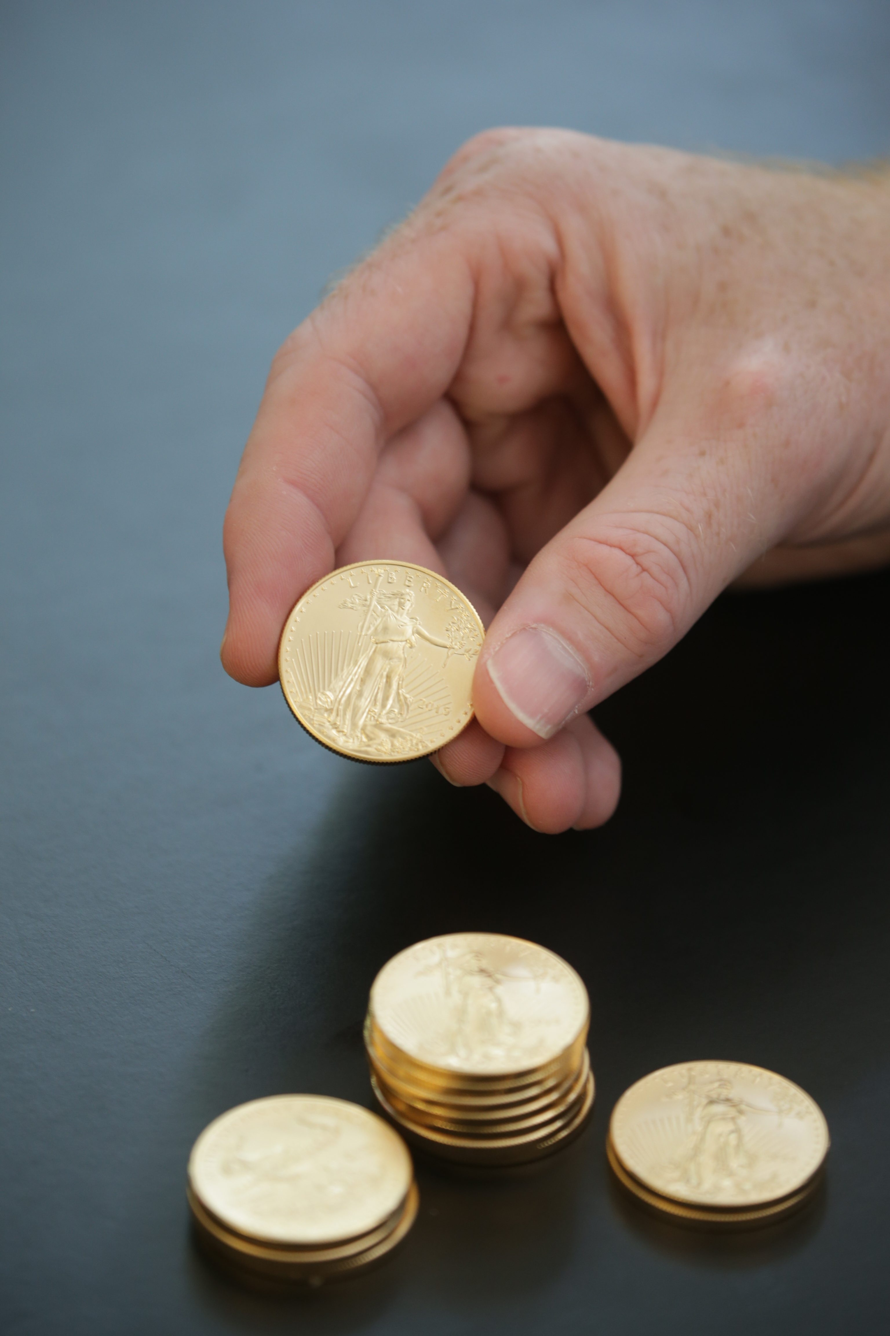 Scott Hunt at Jack Hunt Gold & Silver in Kenmore shows some American Eagle 2015 1-ounce gold coins. (John Hickey/Buffalo News)