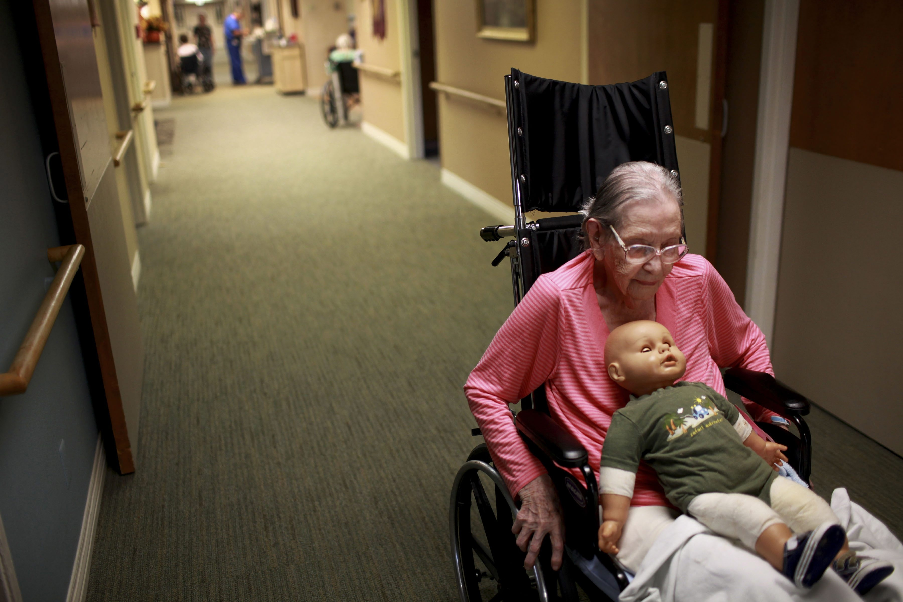 Margaret Nance sits with the doll that has been calming to her at the Beatitudes nursing home in Phoenix, Ariz. Research suggests creating positive experiences for Alzheimer's patients diminishes distress and allows comfort.