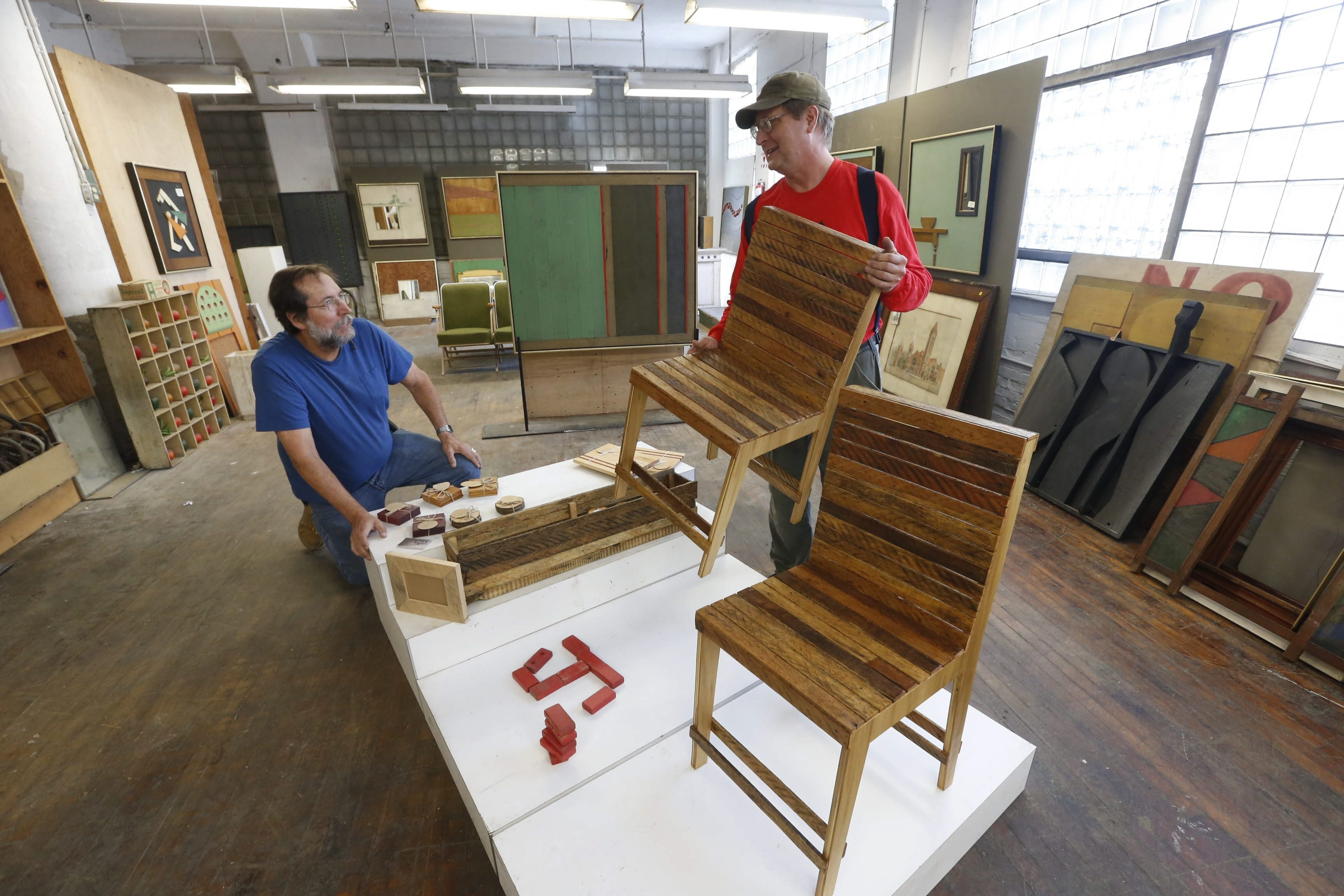 George Apfel, left, and Kevin Hayes arrange recycled art and furniture created by artisan Shawn Faulkner at the new ReUse Action store at 980 Northampton St. in the city's Fillmore section, near the Milk-Bone factory. It's being called Guild @ 980.