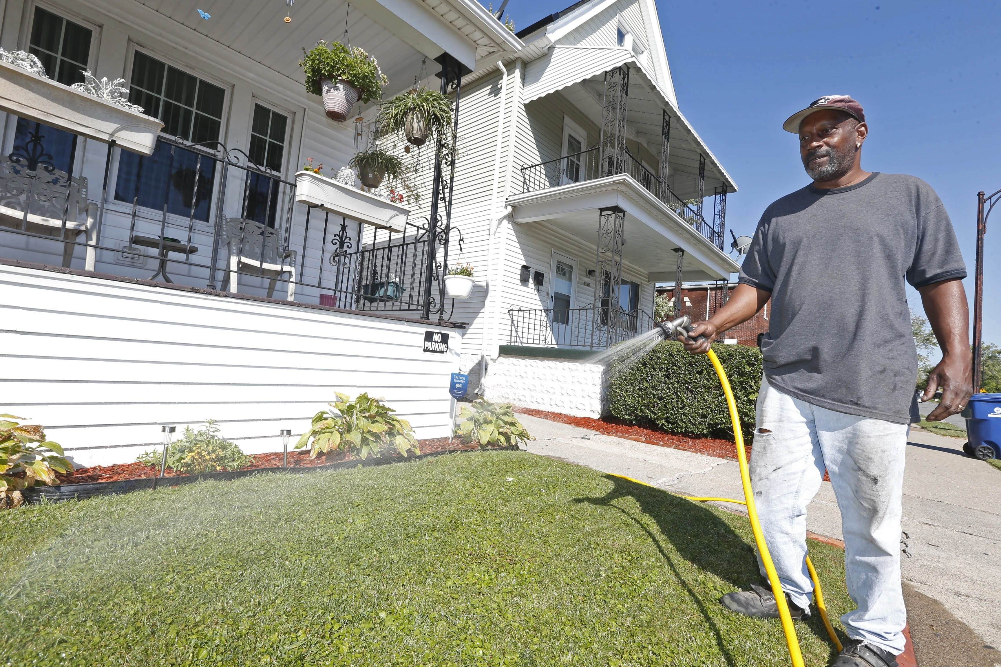 Kenneth Gardner waters his East Ferry Street lawn on a sunny Tuesday, saying he couldn't remember ever doing that so late in the season.