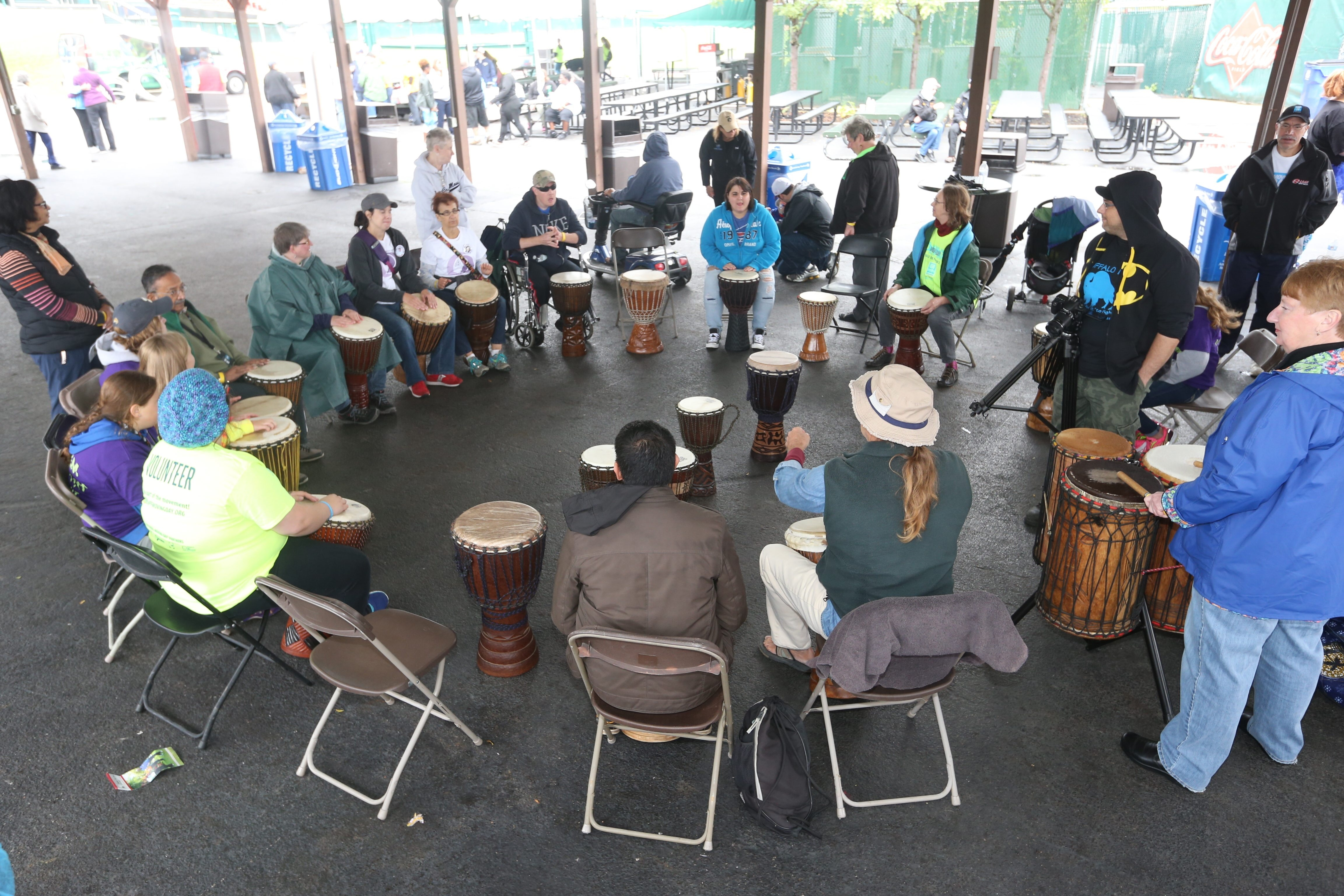 People participate in a drum circle during National Parkinson Foundation of WNY's Moving Day event in Buffalo on Sunday. Despite the rain, about 500 people took part in the annual event, which encourages people to walk, dance and do yoga in support of Parkinson's patients.