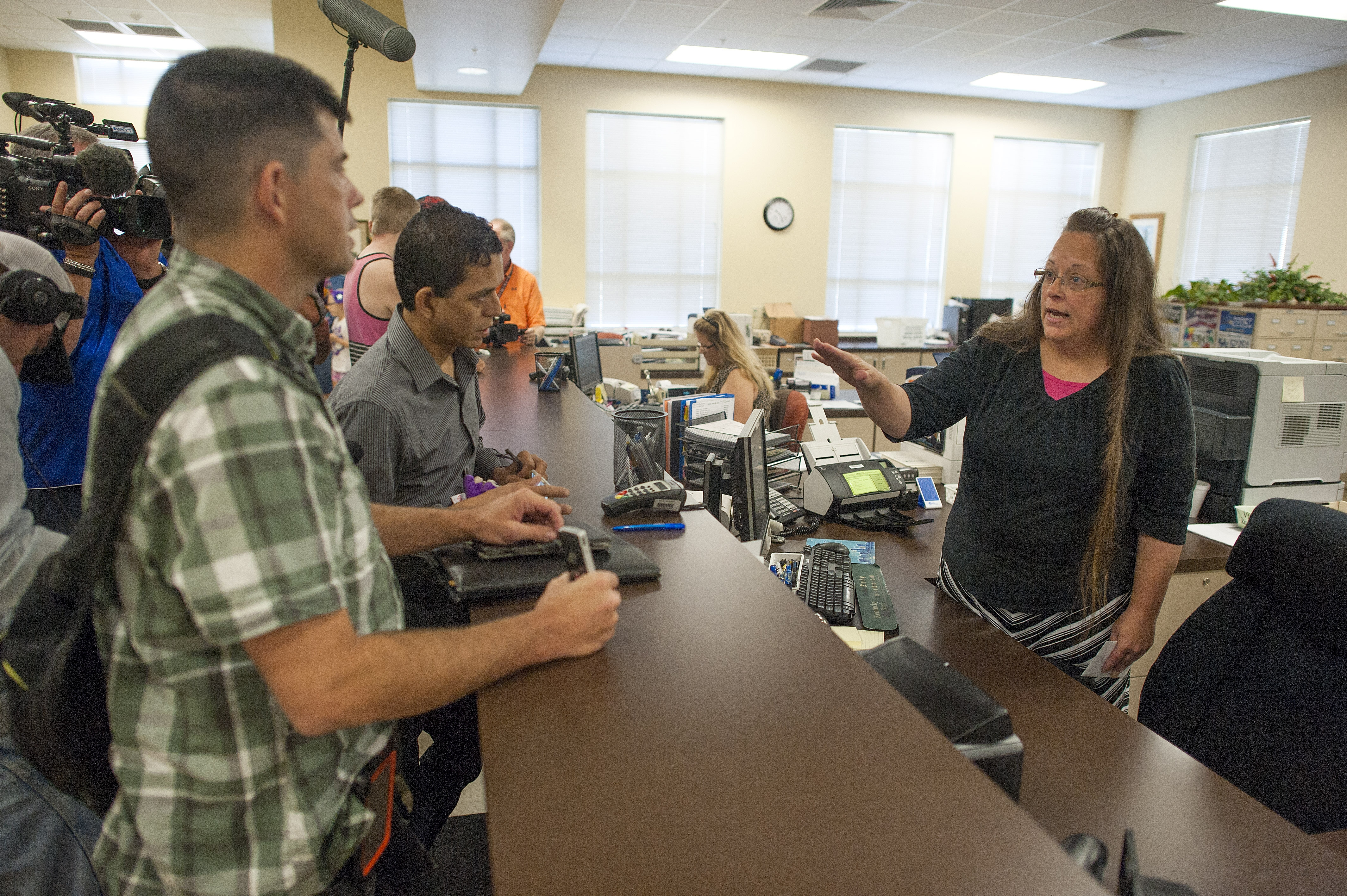 Robbie Blankenship, left, stands next to his partner of 20 years, Jesse Cruz, of Corpus Christie, Texas, as they speak last week with Rowan County Clerk of Courts Kim Davis at the County Clerk's Office in Morehead, Ky. Davis, who cited a religious objection to issuing licenses for same-sex marriage, went to jail, creating an unnecessary crisis. On Monday, the judge who jailed Davis released her.