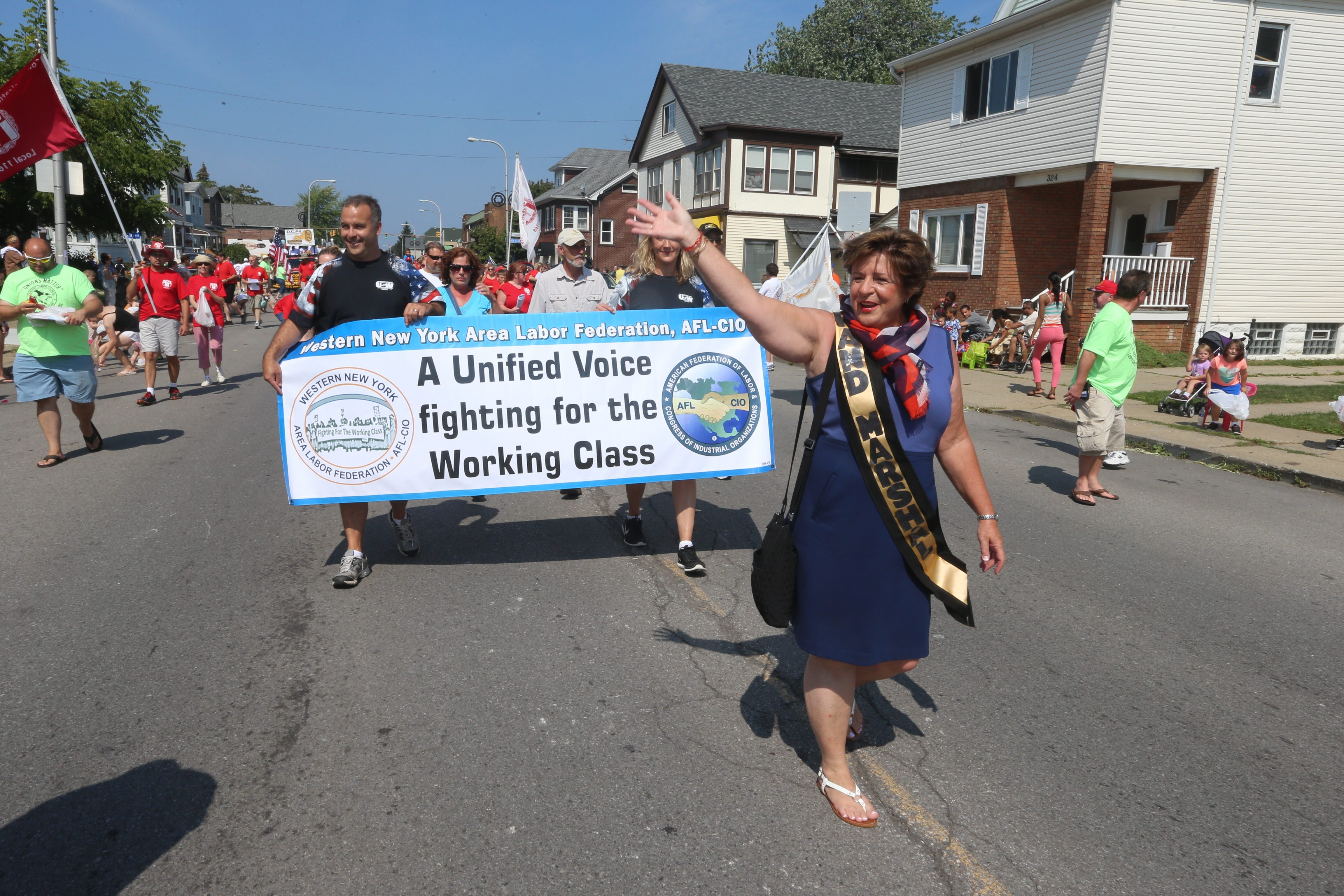 The Buffalo AFL-CIO Council's  Grand Marshal Debbie Hayes, CWA upstate area director, waves to the crowd lining the street as she marches in the annual Labor Day Parade along Abbott Road in South Buffalo on Monday.