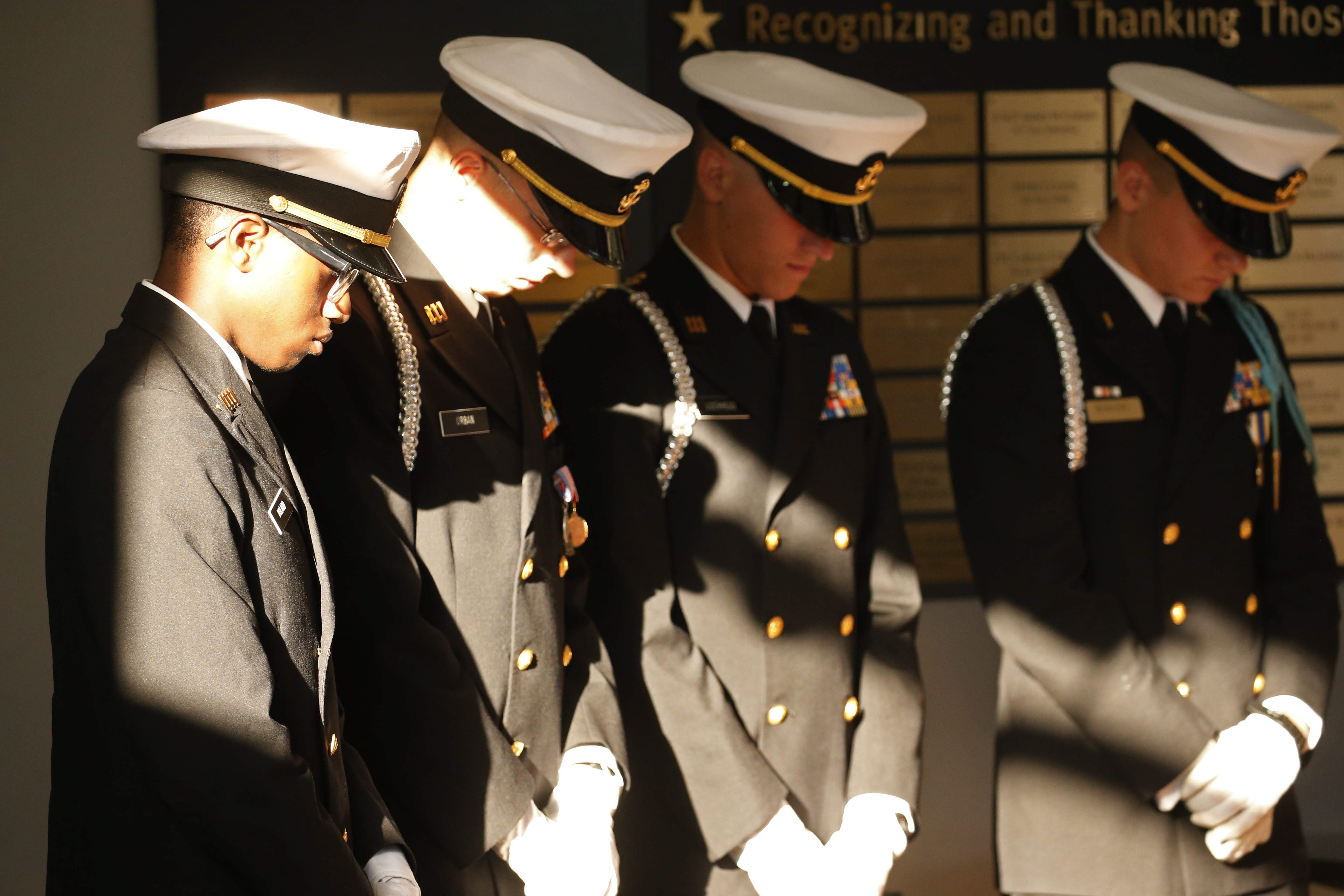 Cadets from the Maritime Charter School Honor Guard bow their heads during a 9/11 remembrance ceremony at the Buffalo and Erie County Naval and Military Park, Friday, Sept. 11, 2015.  From left are Melvin Roland, Douglas Urban, Connor Lochhead and Claudio Benavides.  (Derek Gee/Buffalo News)