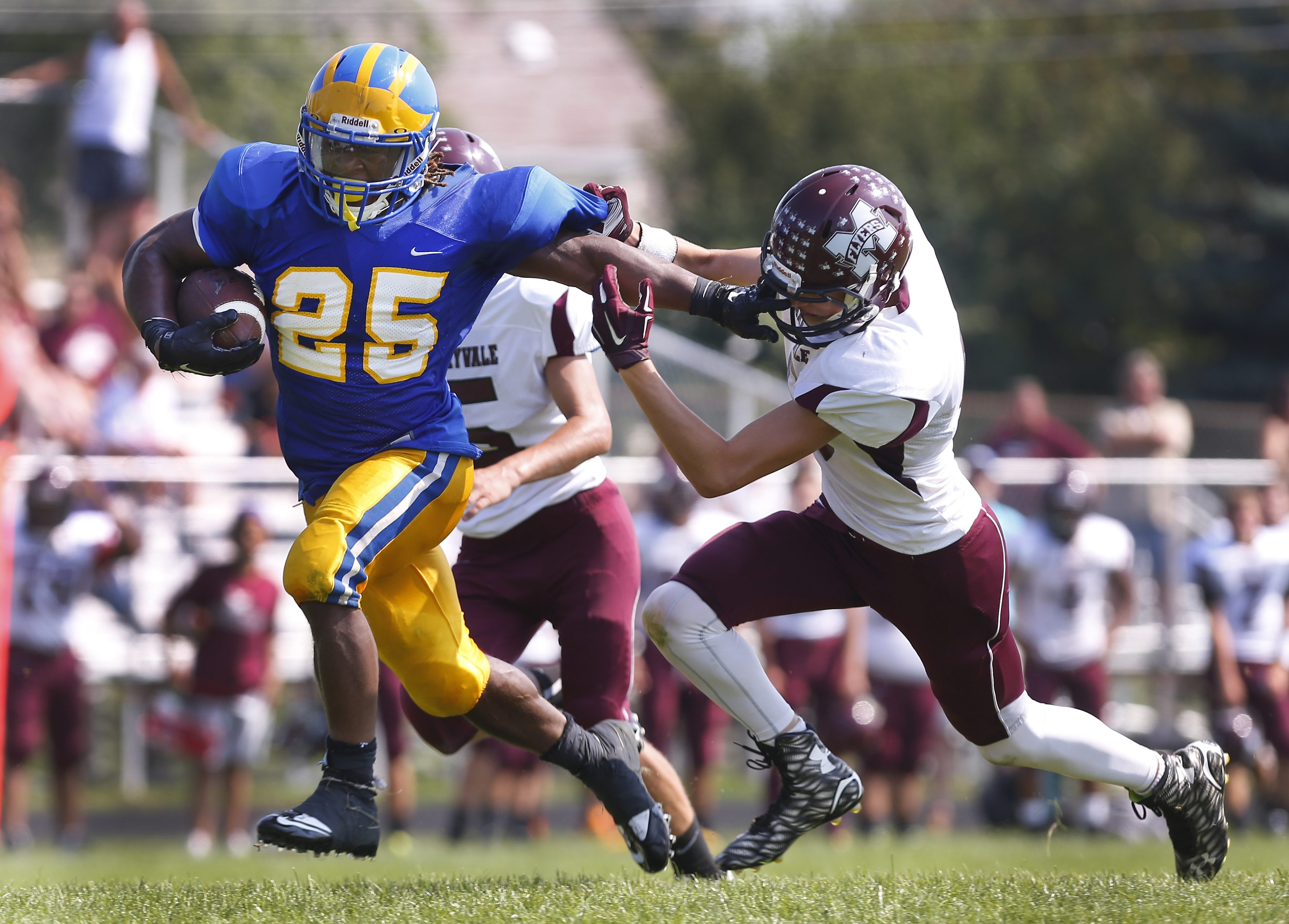 Cleveland Hill's Grayson Taylor stiff arms Maryvale's Andrew Crombie en route to 201 yards of rushing in a Week One win.