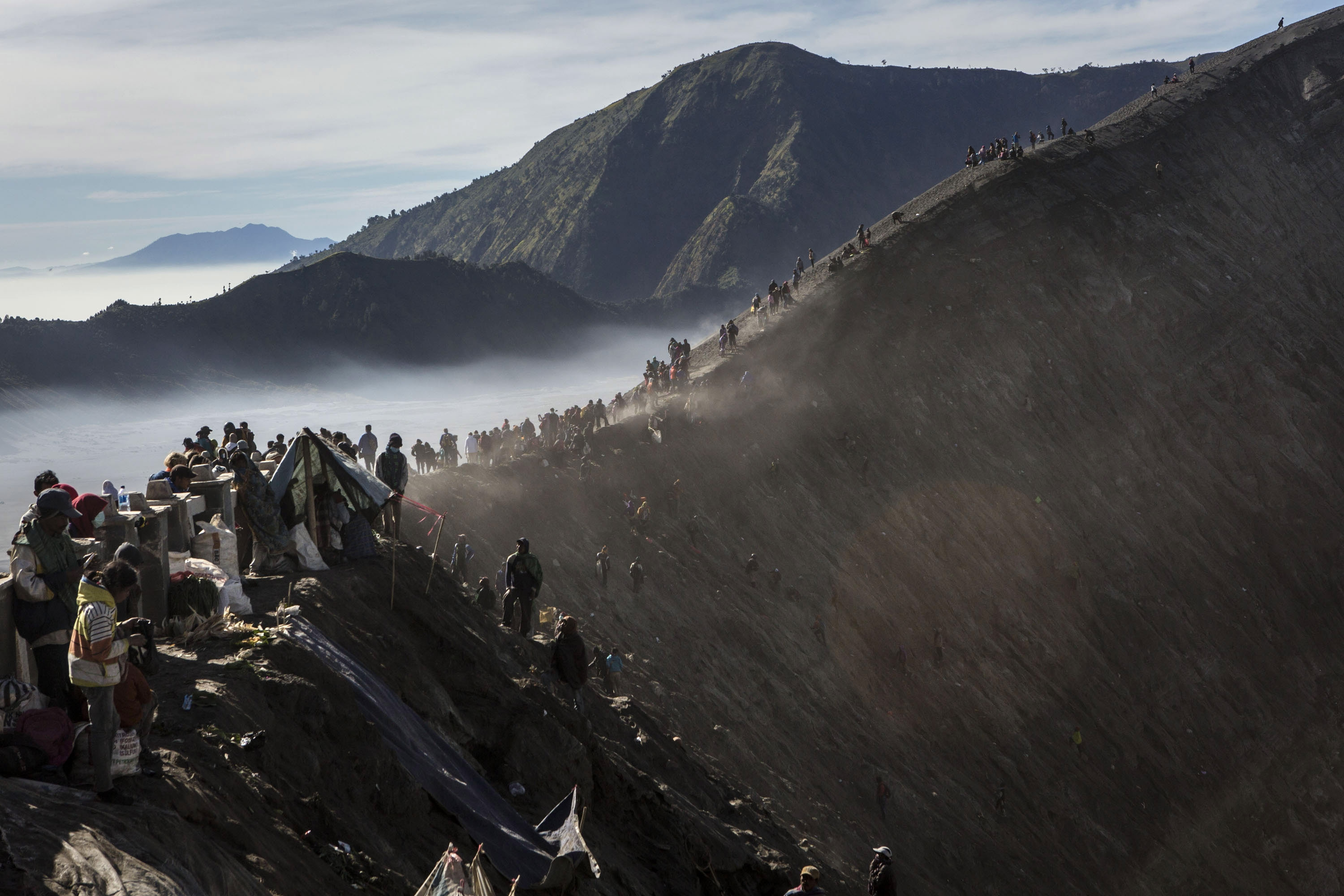 PROBOLINGGO, EAST JAVA, INDONESIA - AUGUST 01:  Tenggerese worshippers gather at the crater of Mount Bromo during the Yadnya Kasada Festival on August 01, 2015 in Probolinggo, East Java, Indonesia. The festival is the main festival of the Tenggerese people and lasts about a month. On the fourteenth day, the Tenggerese make the journey to Mount Bromo to make offerings of rice, fruits, vegetables, flowers and livestock to the mountain gods by throwing them into the volcano's caldera. The origin of the festival lies in the 15th century when a princess named Roro Anteng started the principality of Tengger with her husband Joko Seger, and the childless couple asked the mountain Gods for help in bearing children. The legend says the Gods granted them 24 children but on the provision that the 25th must be tossed into the volcano in sacrifice. The 25th child, Kesuma, was finally sacrificed in this way after initial refusal, and the tradition of throwing sacrifices into the caldera to appease the mountain Gods continues today. (Photo by Ulet Ifansasti/Getty Images) *** BESTPIX ***