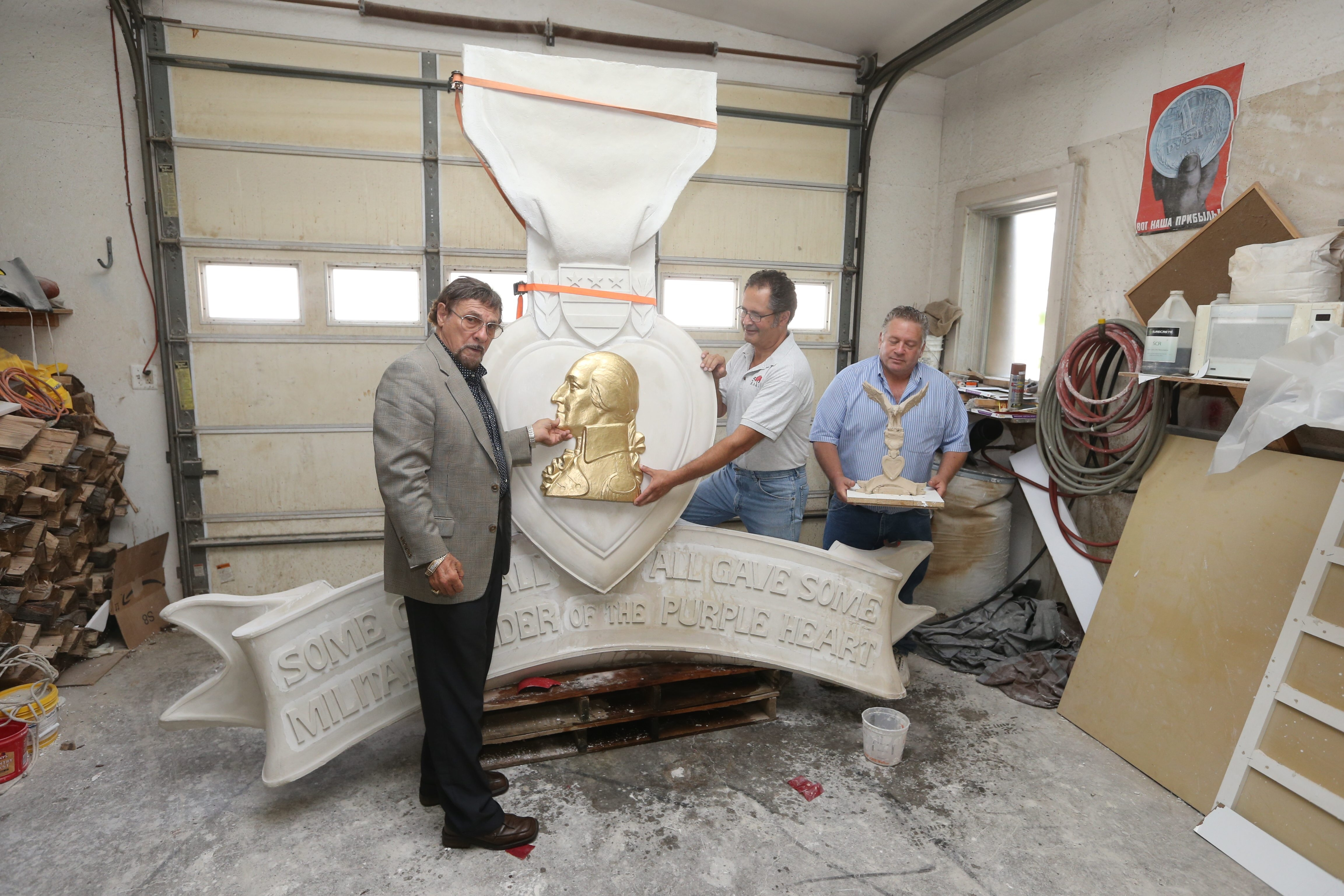 Artist Donald R. Parrino, left, sculptor Leo Lysy, center and Gary Bolles examine the Purple Heart Medal sculpture that will be on display at Heroes and Patriots Park in Lancaster.
