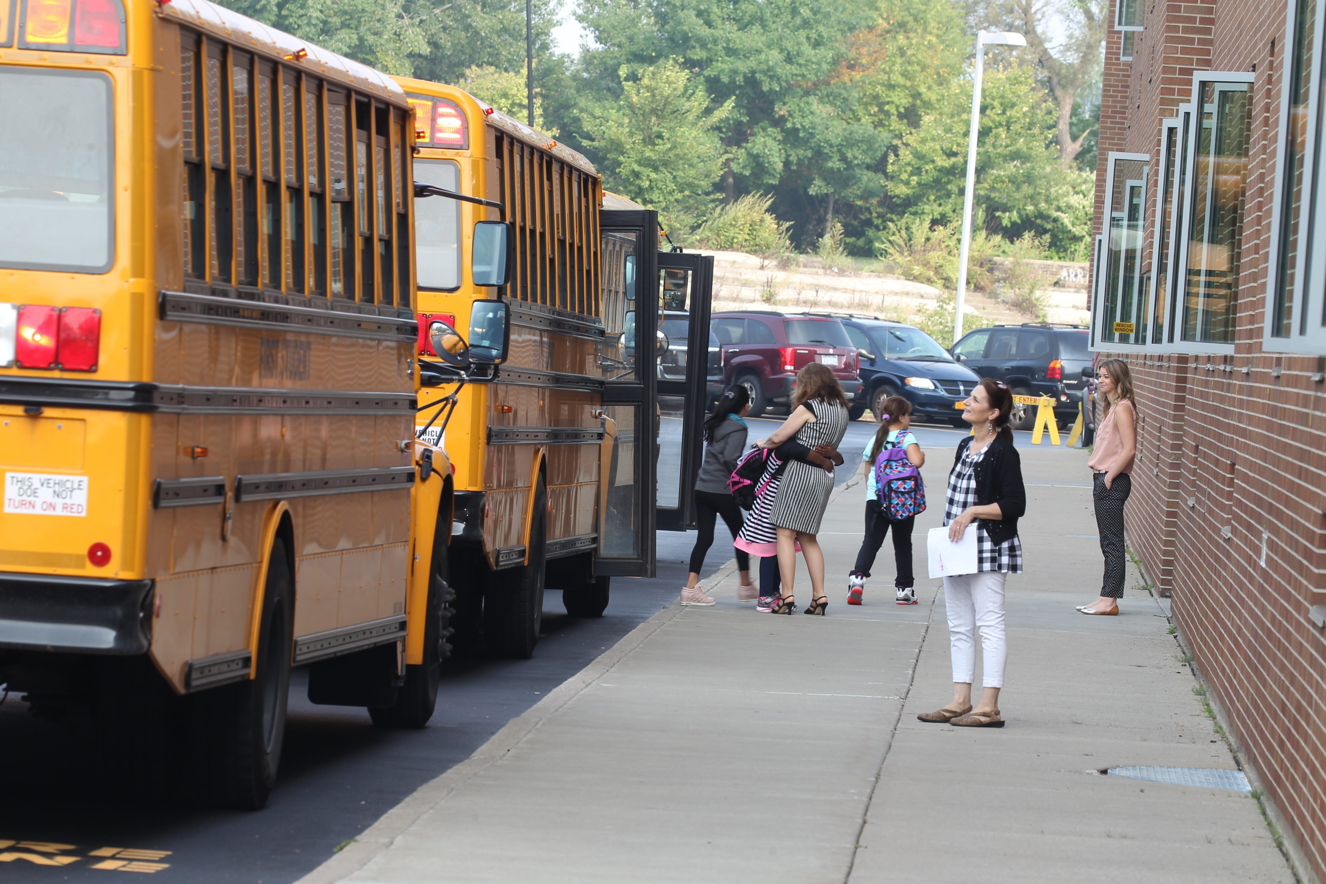 Children arrive on the first day of school at South Side Elementary and Pricipal Darlene Jesonowski gets a hug from a student Thursday,  Sept. 3, 2015.  (John Hickey/Buffalo News)
