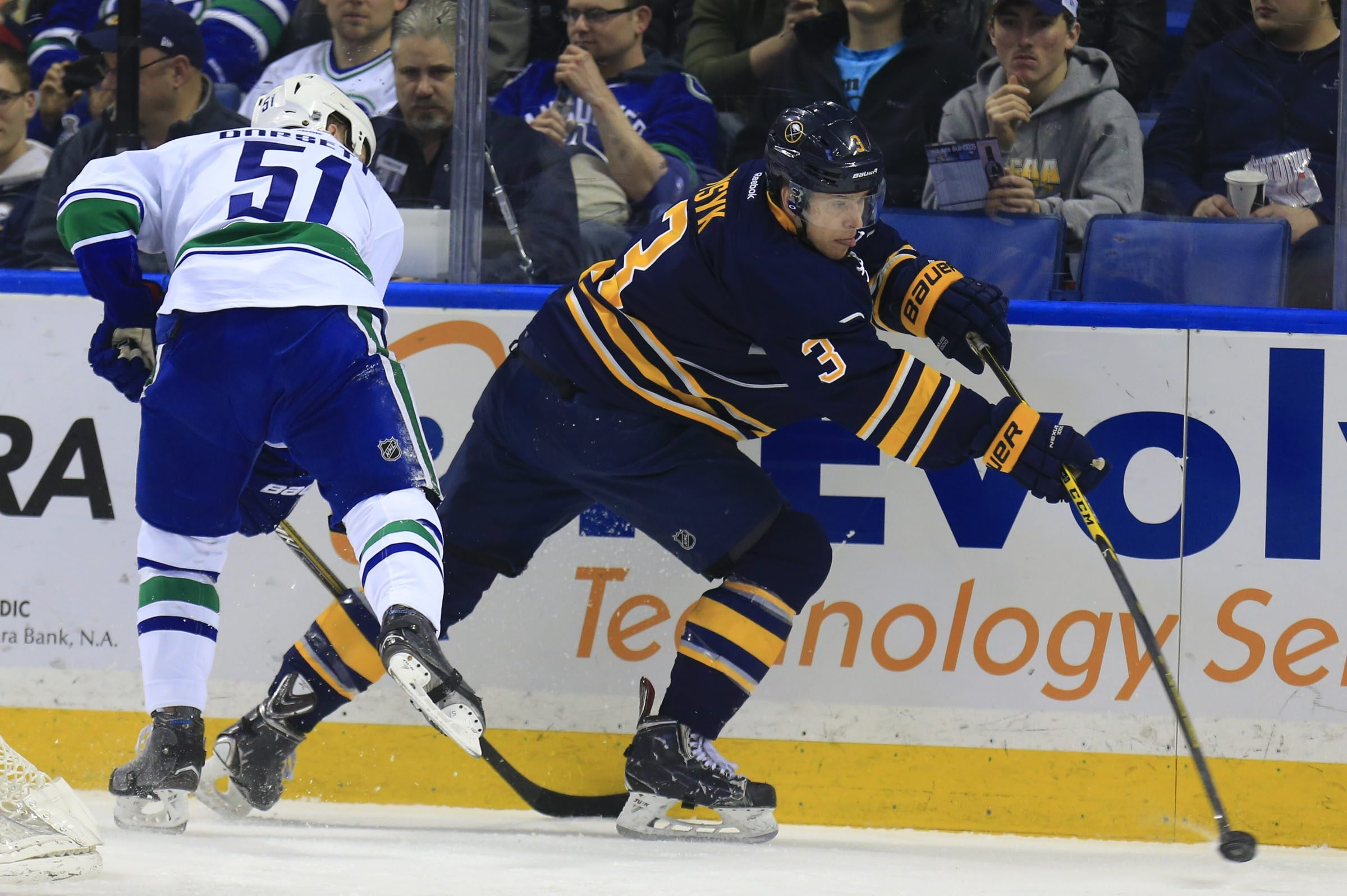 2LINE CUTLINE Buffalo Sabre Mark Pysyk moves the puck past Vancouver Canuck Derek Dorsett during first period action at the First Niagara Center on Thursday, Feb. 26, 2015.(Harry Scull Jr./Buffalo News)