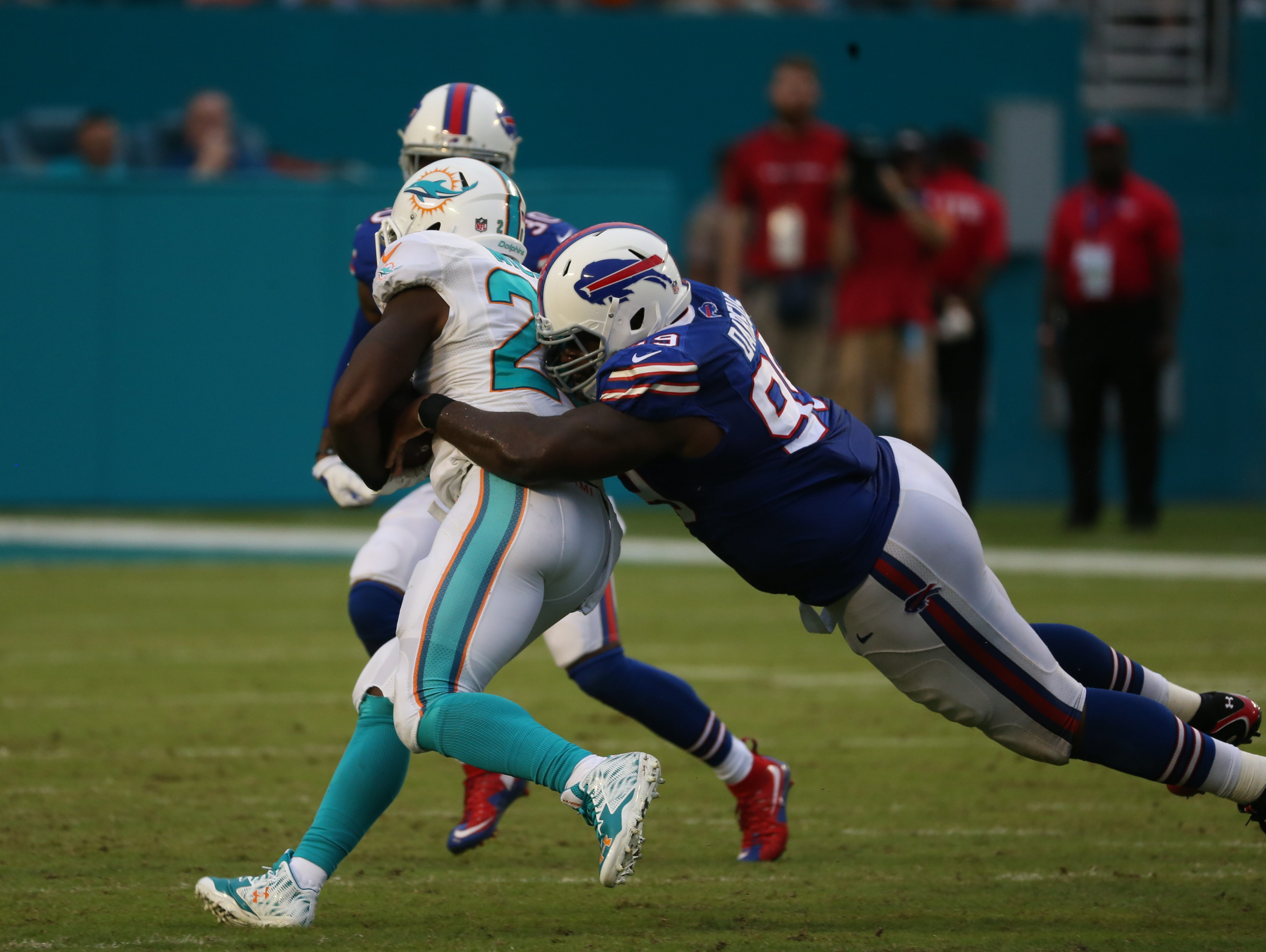 Miami Dolphins running back Lamar Miller (26) is tackled by Buffalo Bills defensive tackle Marcell Dareus (99) during the third quarter on Sept. 27, 2015. (James P. McCoy/ Buffalo News)
