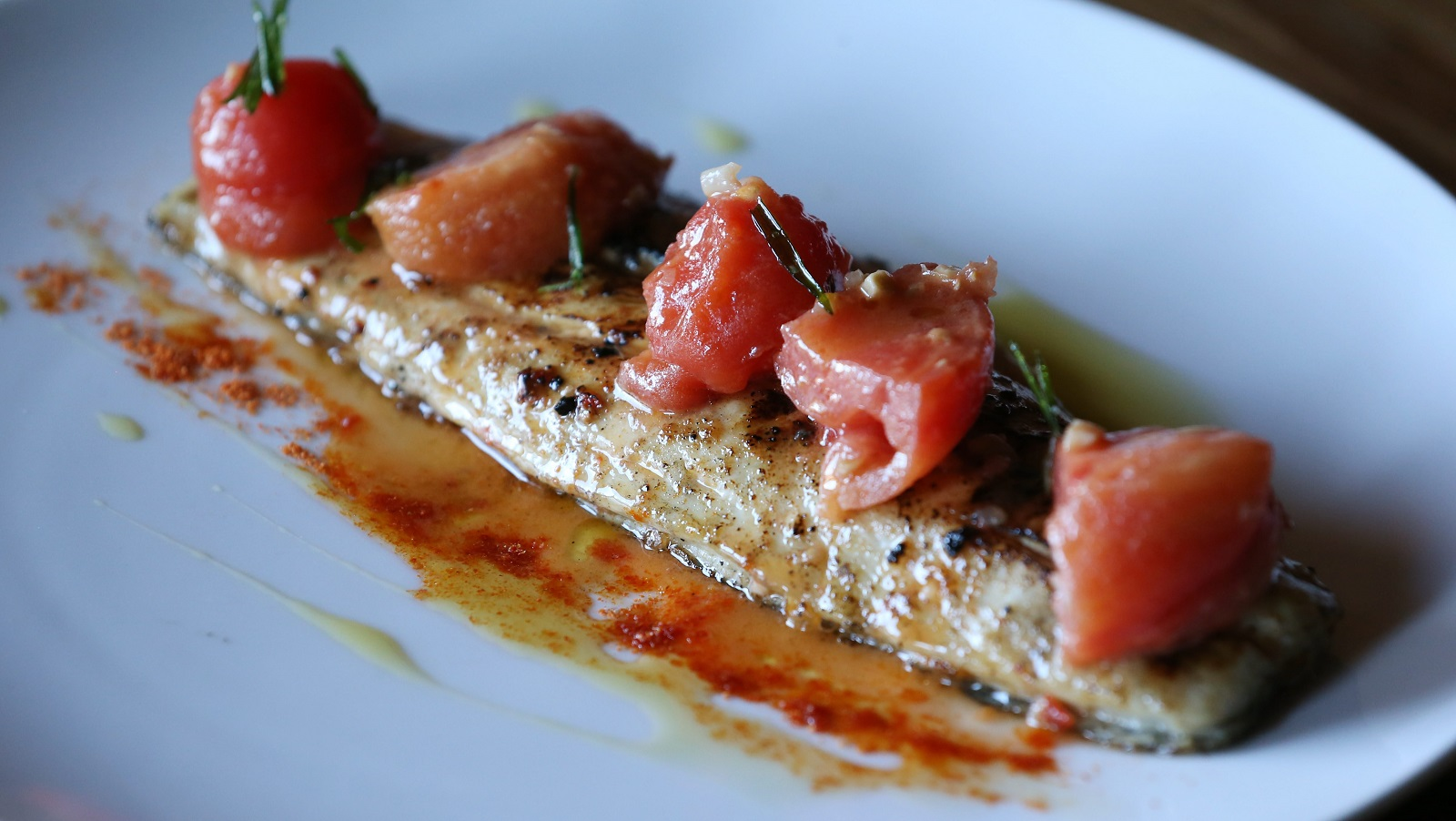 "Toutant's wood-grilled Gulf red drum fish ""on the half shell"" is topped with a vinaigrette marinade and stewed preserved tomatoes. (Sharon Cantillon/Buffalo News)"