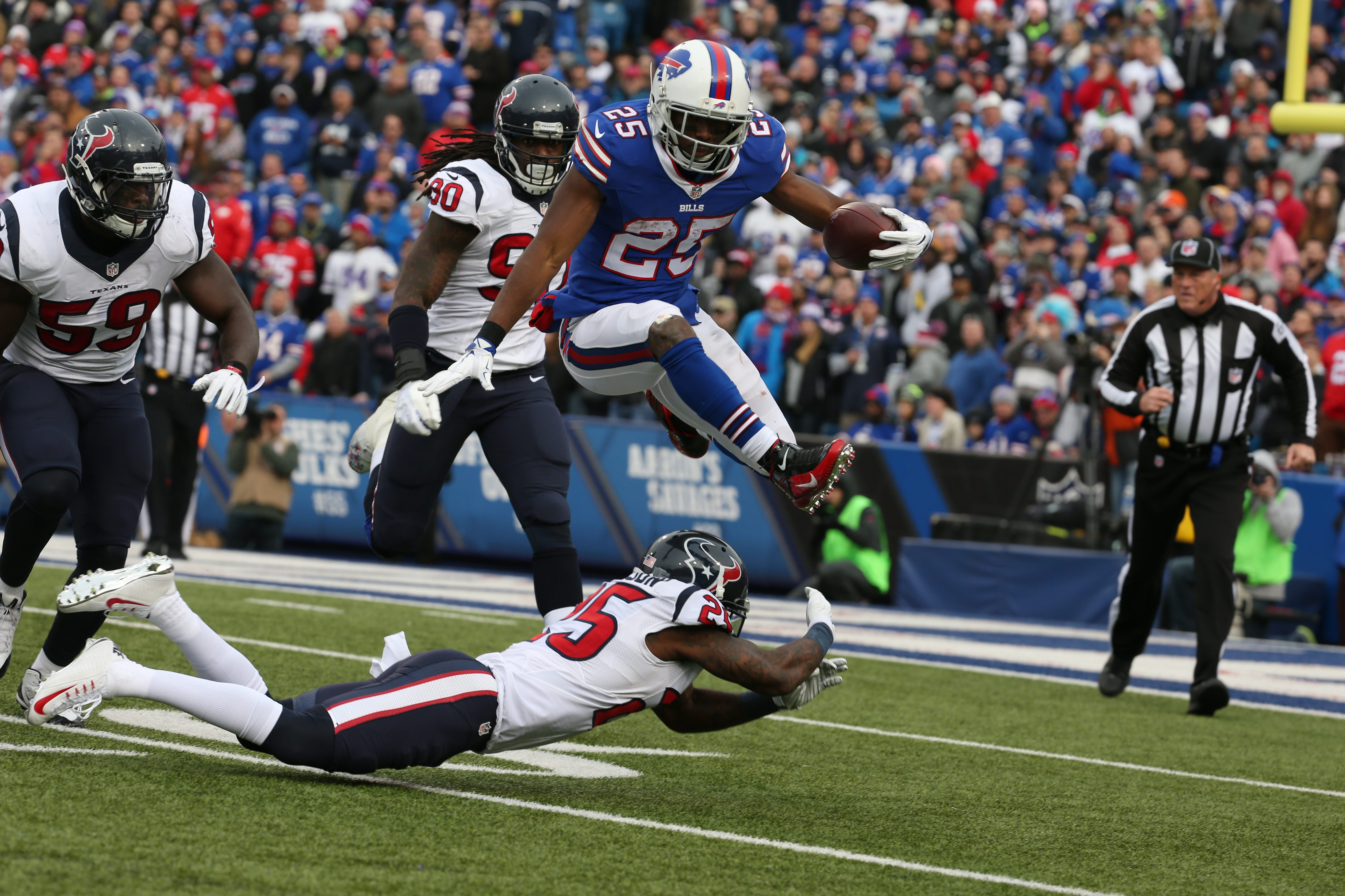 Buffalo Bills running back LeSean McCoy (25) leaps over Houston Texans cornerback Johnathan Joseph (25) during the third quarter at Ralph Wilson Stadium on Dec. 6.  (James P. McCoy/ Buffalo News)