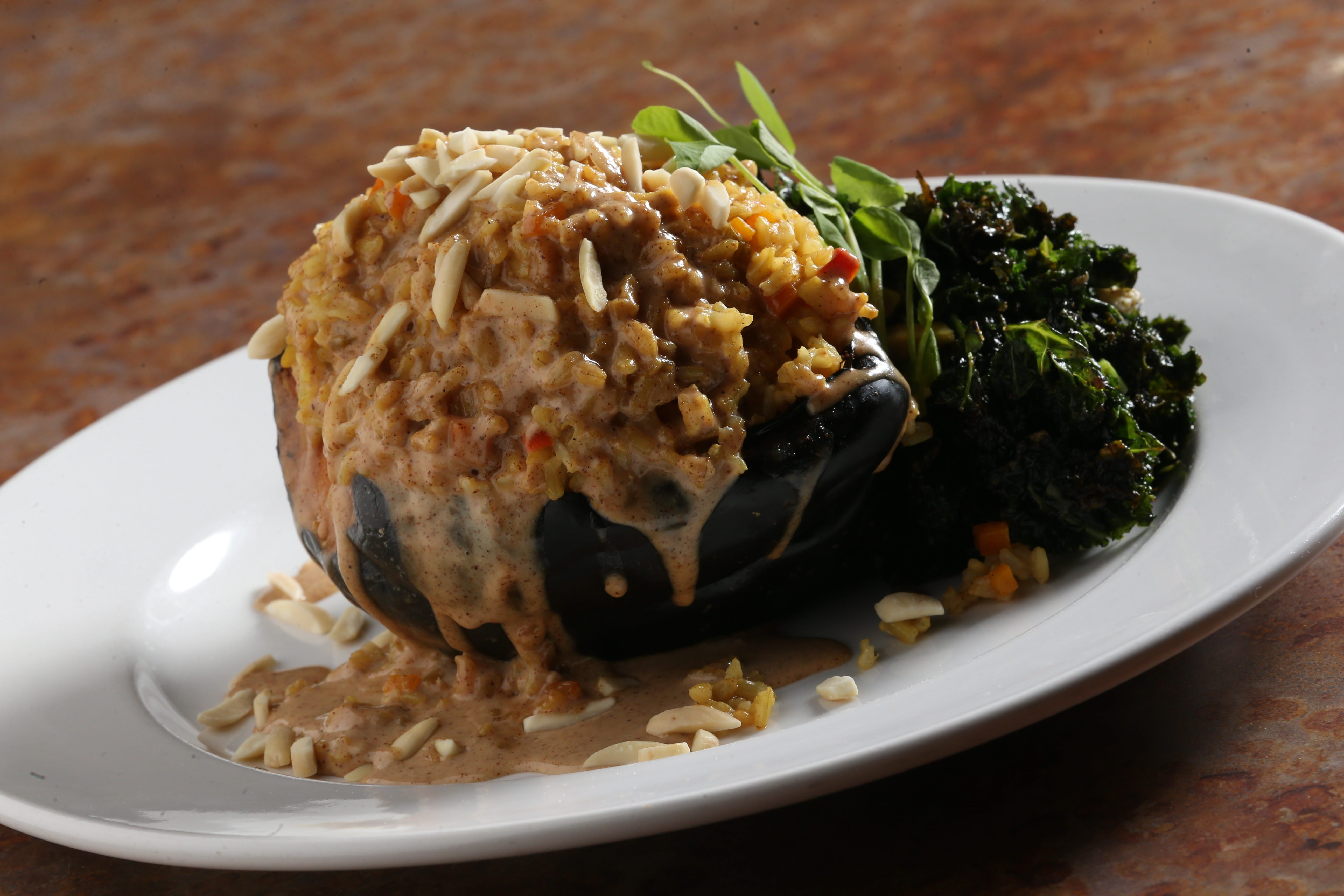 Acorn squash with el ras hangout seasoned basmati rice, garbanzo beans, golden raisins, slivered almonds, kale in a ginger coconut almond sauce. Chicken or shrimp may be added.