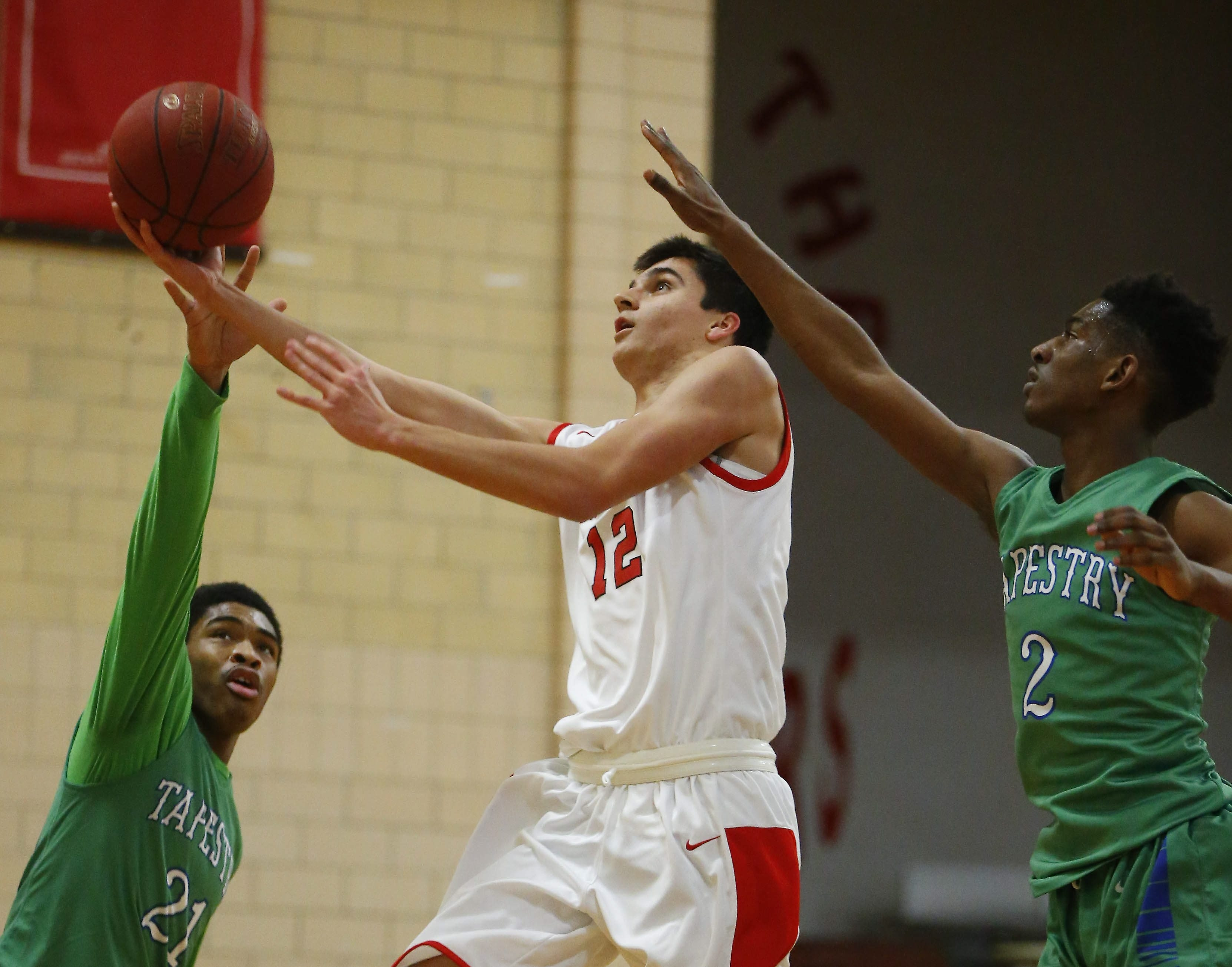Lancaster's Alex Konst drives to the hoop on Tapestry's Paitwan Jenifer, left, and DaVonte Cunningham, right. Konst had 14 points and 14 rebounds for Lancaster in its 64-60 victory.