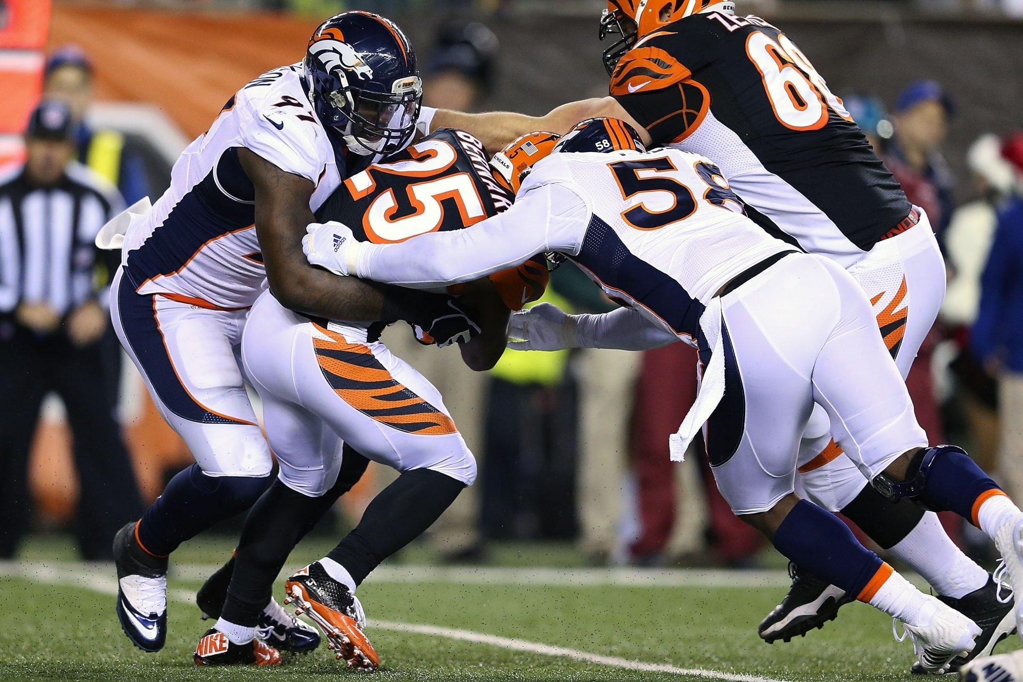 Denver defenders Malik Jackson and Von Miller team up to tackle Cincinnati's Giovani Bernard during last year's meeting between the teams at Paul Brown Stadium. The Broncos and Bengals meet again in Denver Monday night.