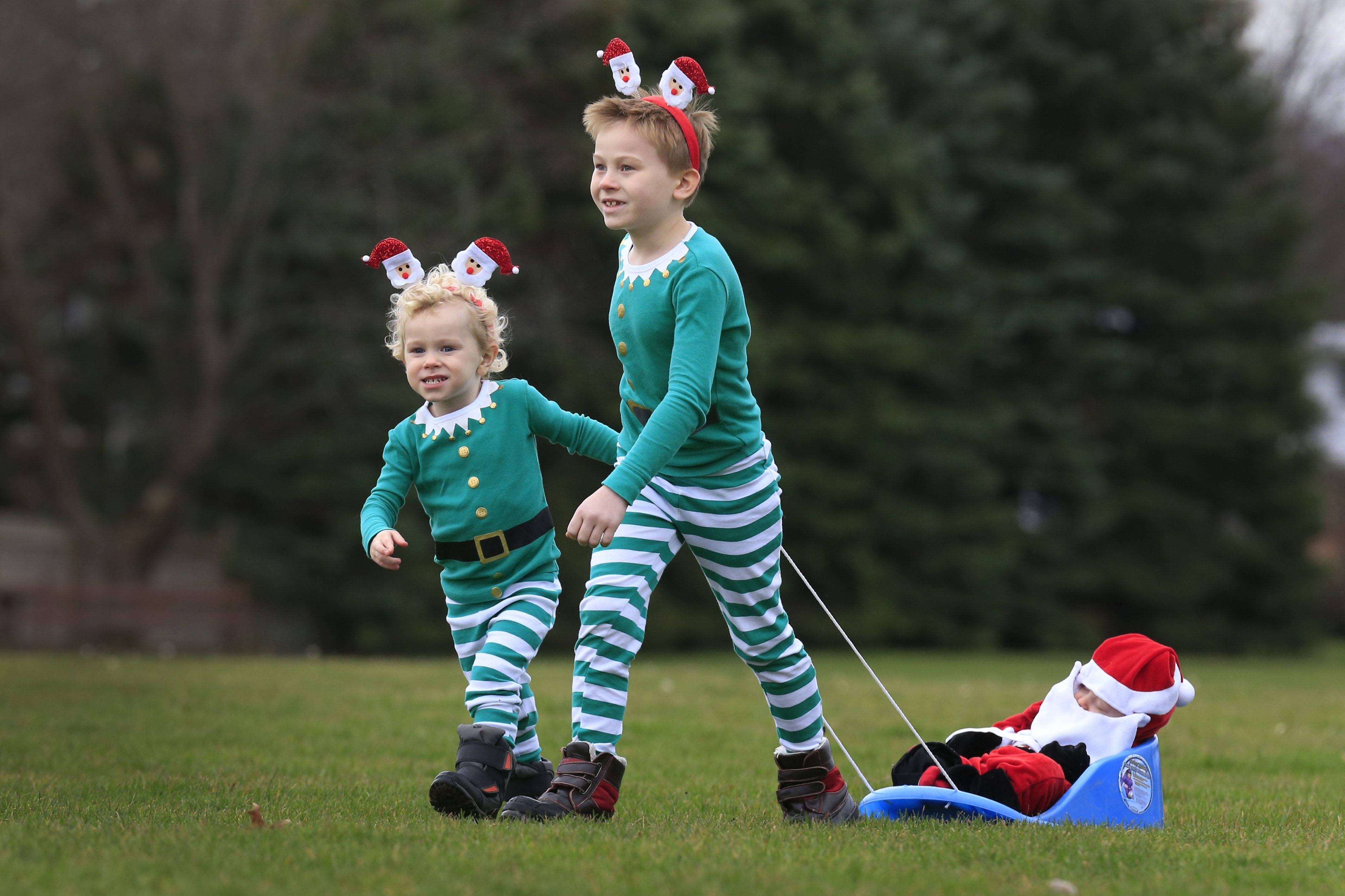 Roman Johnson, 8, and his brother, Landon Litzinger, 3, dressed as elves, pull their brother Hayden Litzinger, 9 months, dressed as a baby Santa in their backyard Friday.