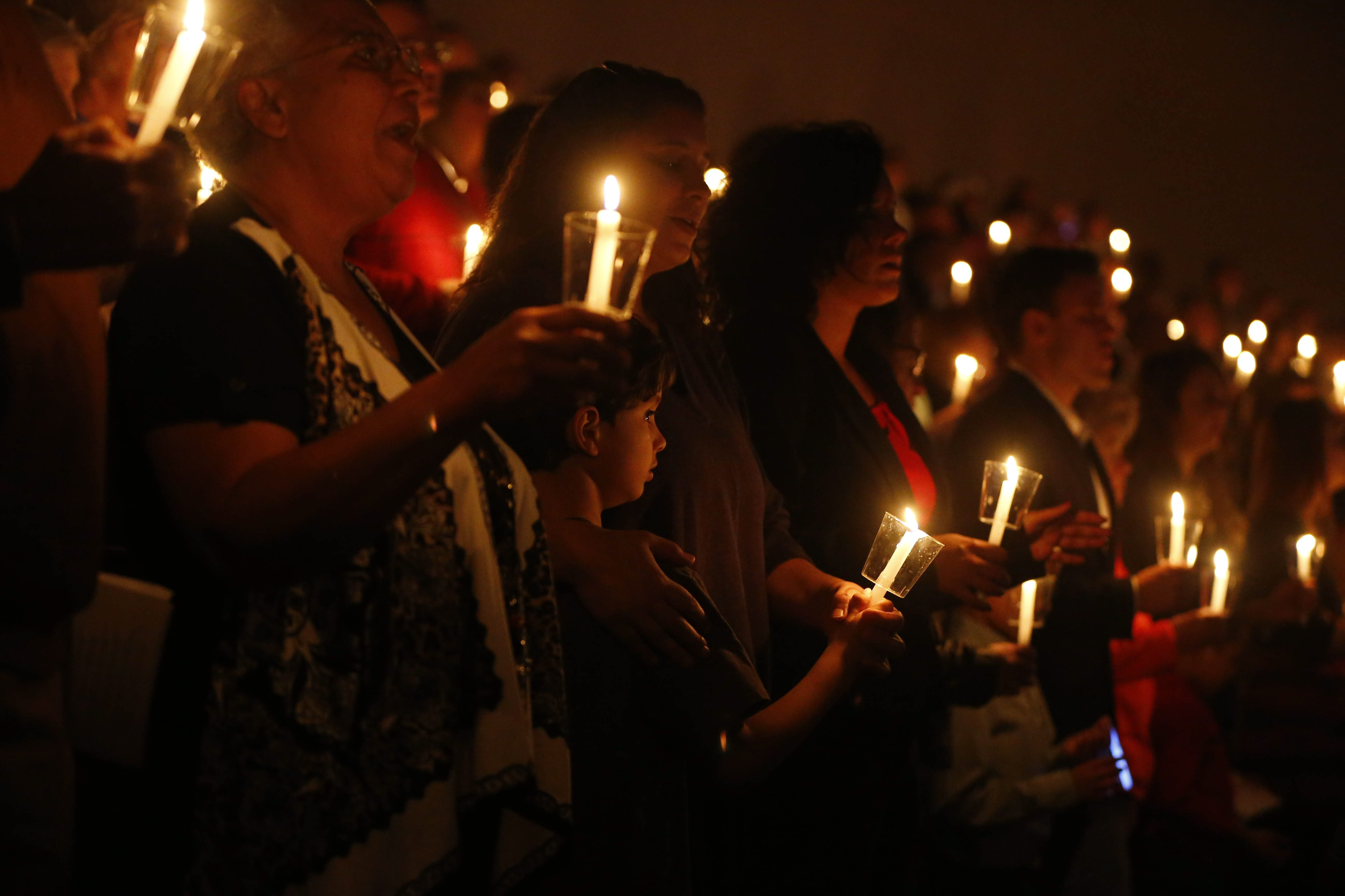 People hold candles and sing carols during Christmas Eve service at the Chapel at CrossPoint, a nondenominational church  in Amherst, on Thursday.