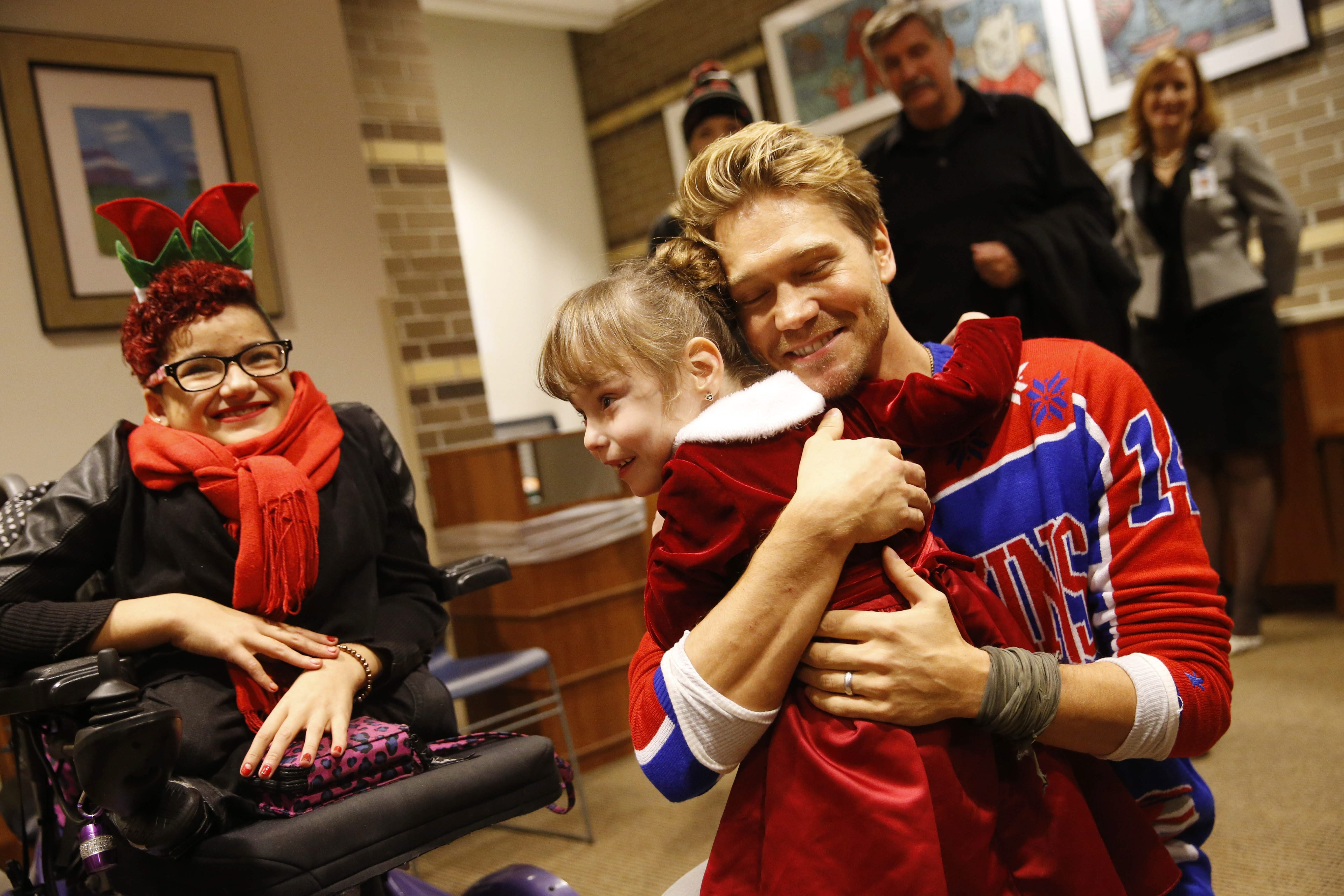 The actor Chad Michael Murray hugs 5-year-old Ava Hackett of Darien Center as Natalie Rivera, 17, left, looks on at Women and Children's Hospital on Wednesday.