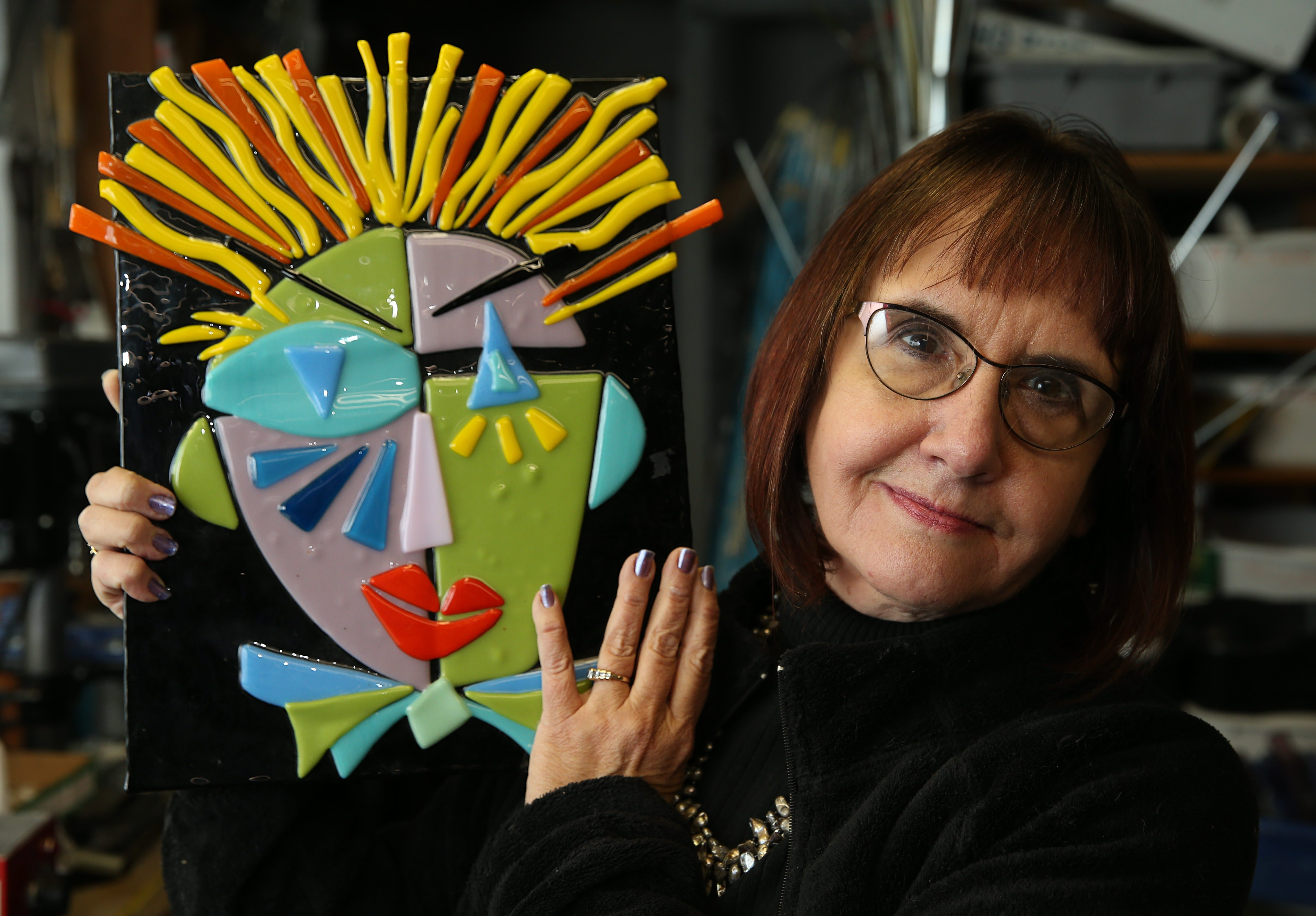 Artist Catherine O'Connor holds a self-portrait created in fused glass at her shop, ArtFX Glass, in Newfane. She'll be exhibiting at Lockside Art Center beginning Tuesday.
