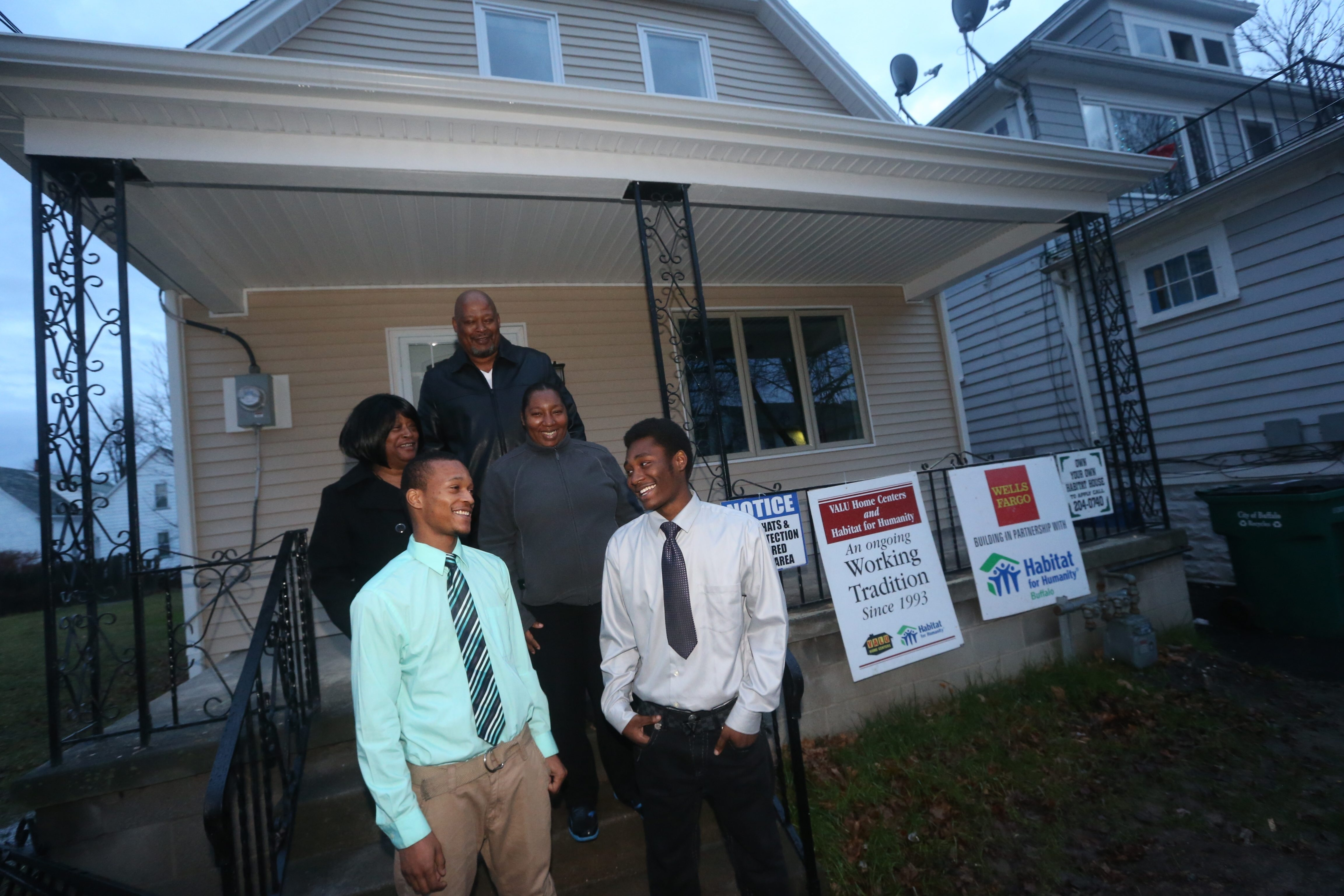 Performing Arts students Corey Hill, left, with his mother, Velma Benson, and Nicholas Toomes, with his parents, Nathanial and Thelma Askew, beam with pride at Habitat for Humanity house they helped build. (John Hickey/Buffalo News)